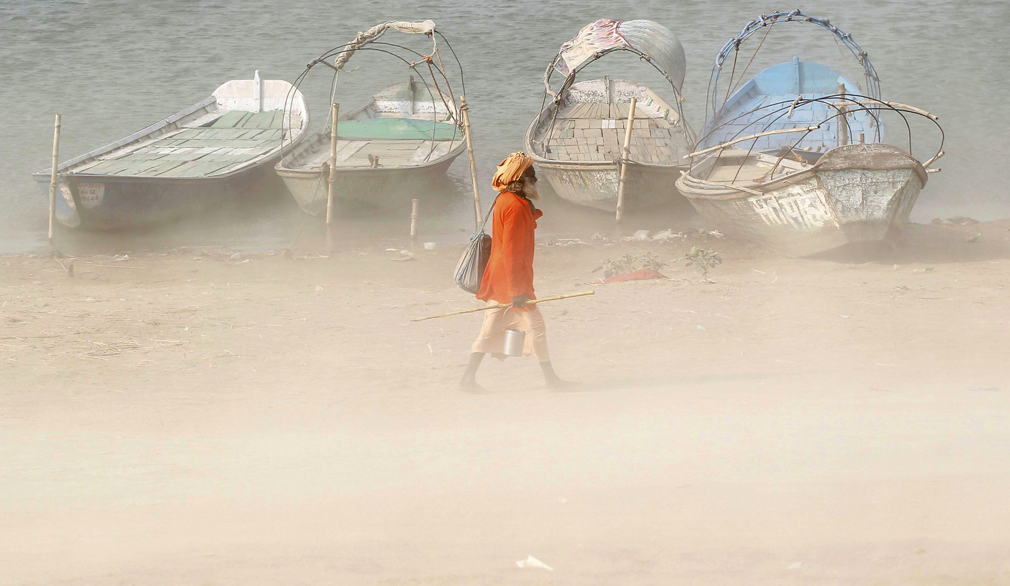 A Sadhu or a Hindu holy man walks on the banks of the river Ganges during a dust storm in Allahabad, India, June 9, 2016. REUTERS/Jitendra Prakash