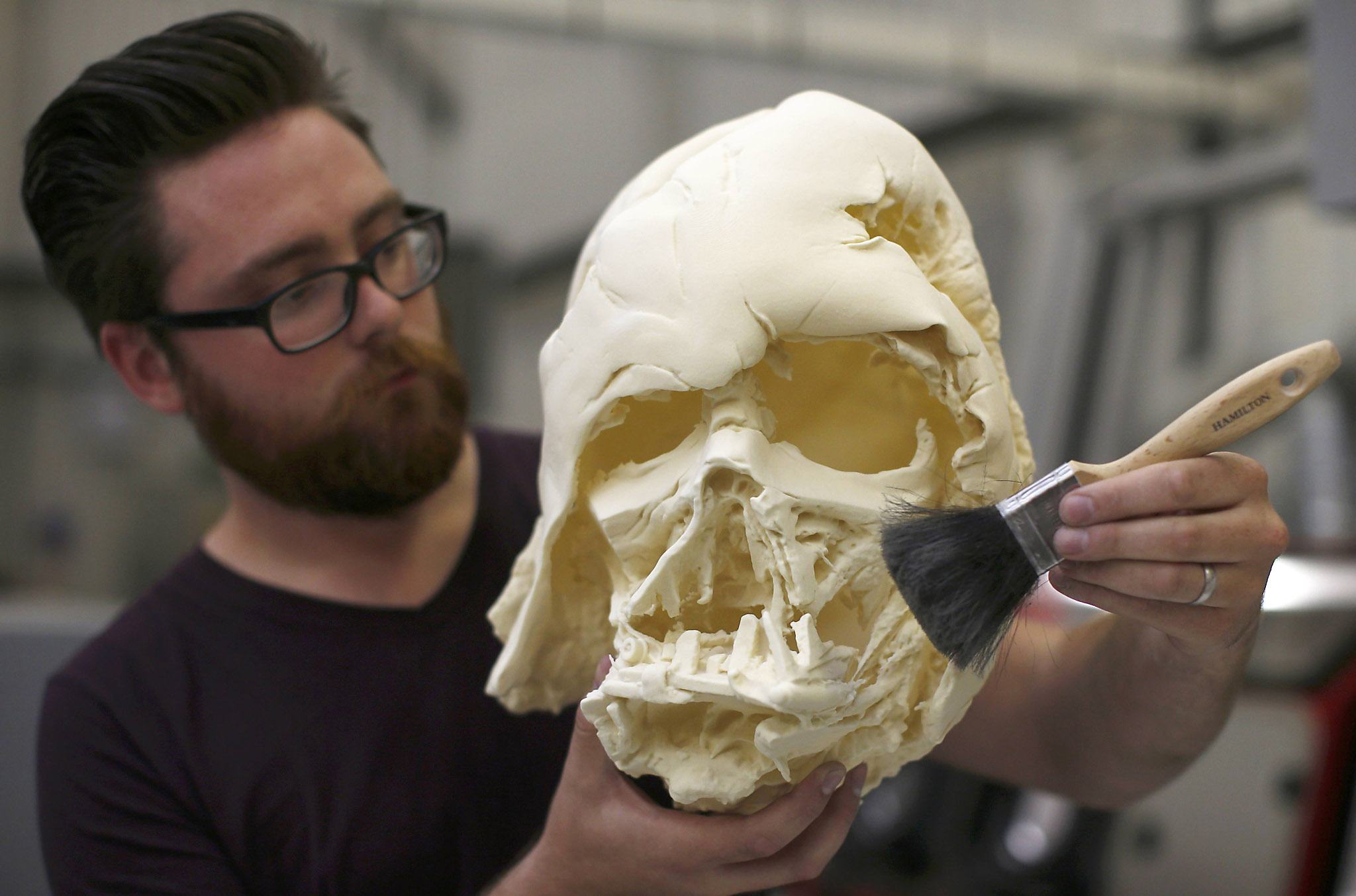 """technician holds a recently 3D printed replica of Darth Vader's melted helmet from """"Star Wars: The Force Awakens"""", in the Propshop headquarters at Pinewood Studios near London, Britain May 25, 2016.  REUTERS/Peter Nicholls"""