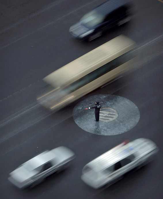A police officer directs traffic in the rain as a dignitary's motorcade passes through an intersection in central Beijing, China, Friday, June 17, 2016. Although Beijing is in a semi-dry climate, it receives much of its annual precipitation during the summer months. (AP Photo/Mark Schiefelbein)