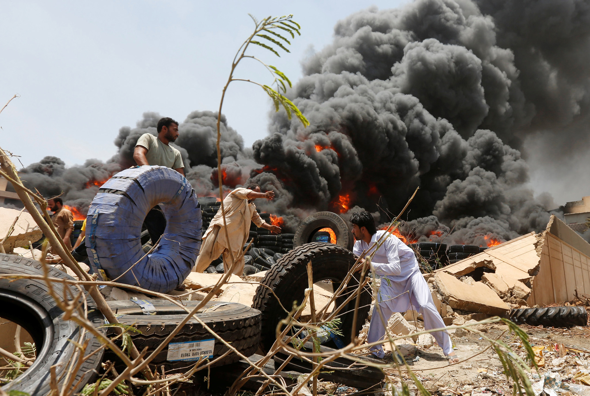 Workers move tires from a warehouse after a fire broke out at an industrial zone in Karachi, Pakistan
