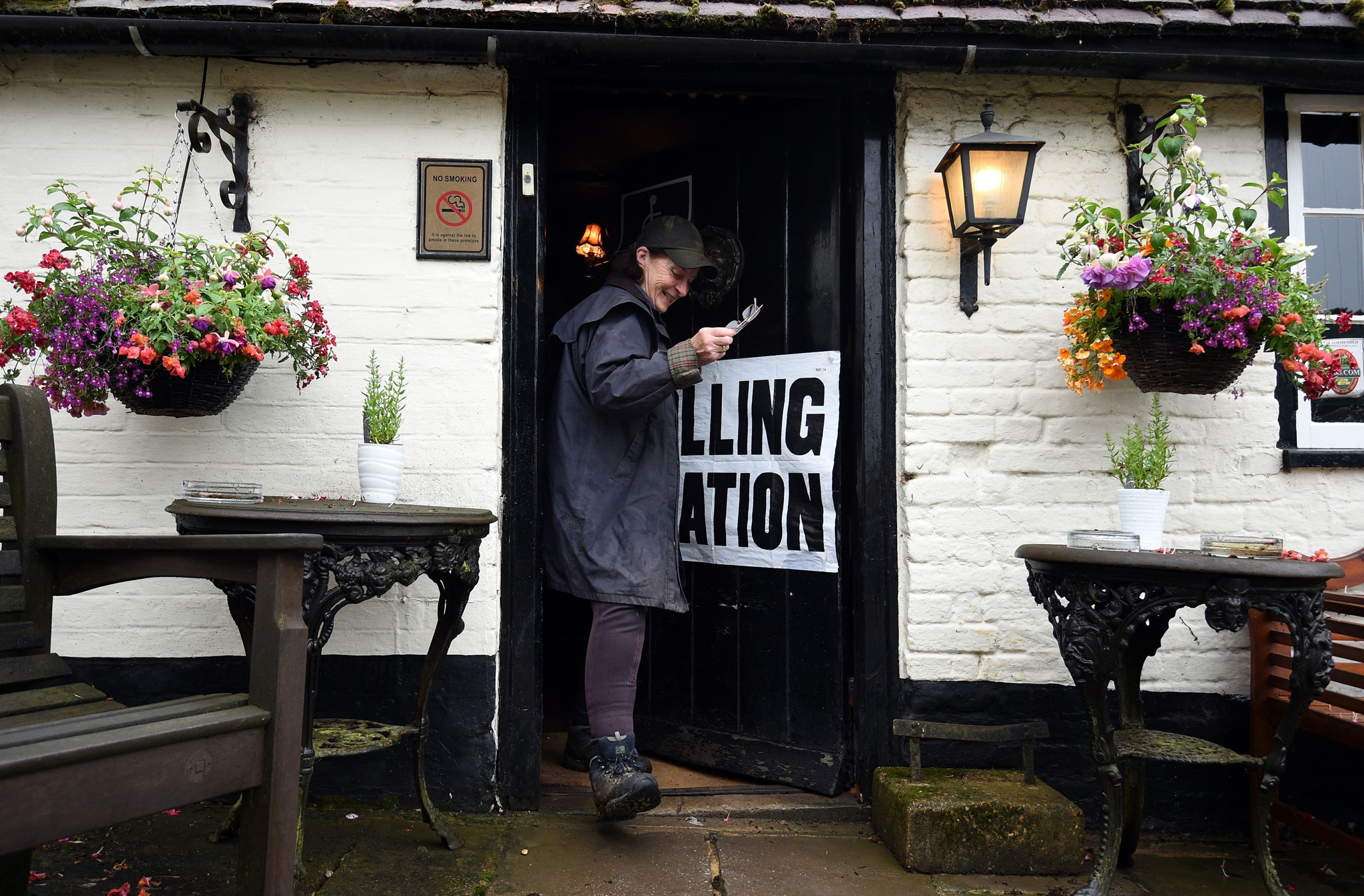 A member of the public leaves a polling station at the White Horse Inn in Priors Dean, Hampshire