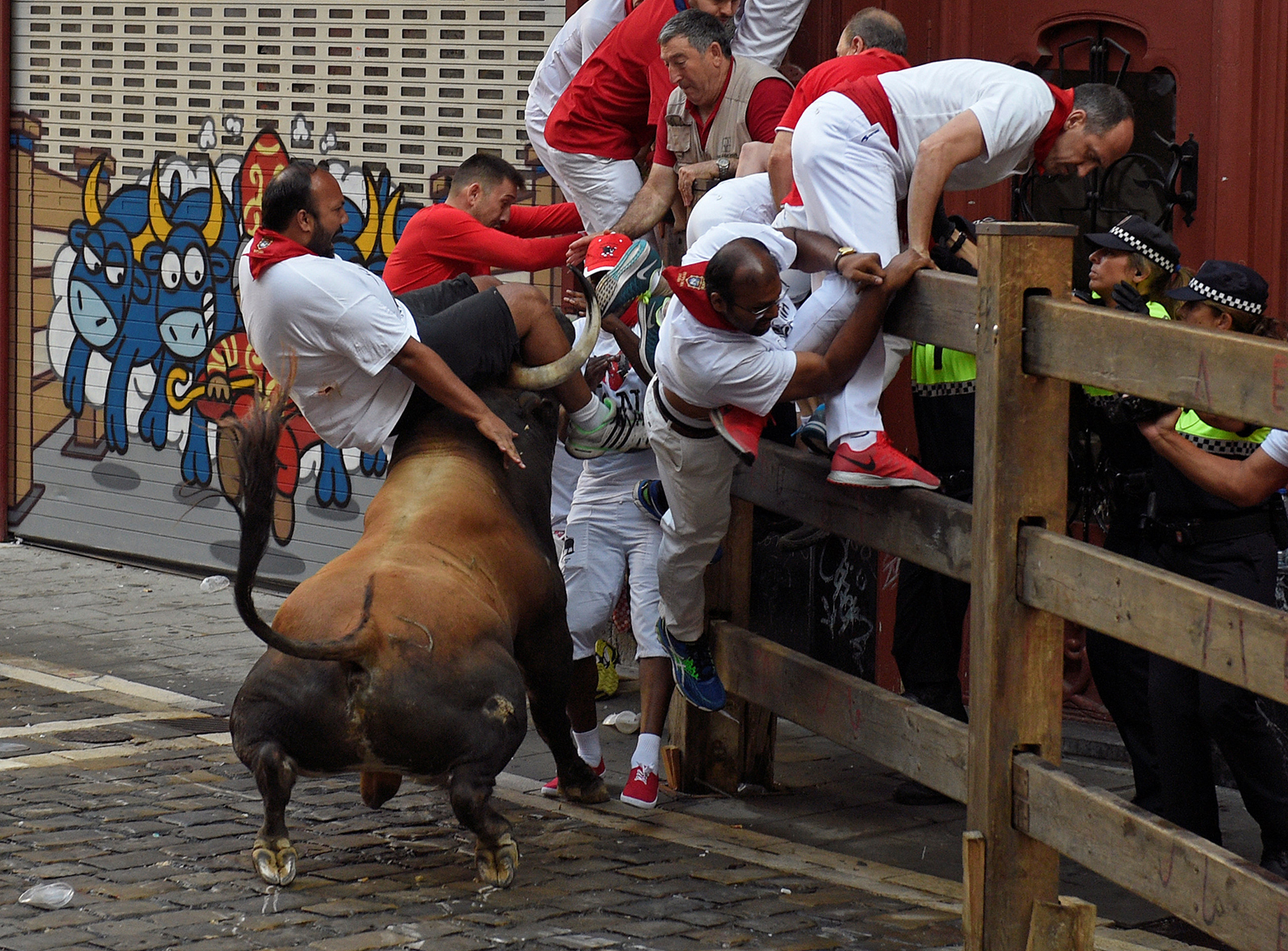 A runner is thrown by a Cebada Gago fighting bull at Estafeta corner during the second running of the bulls at the San Fermin festival in Pamplona