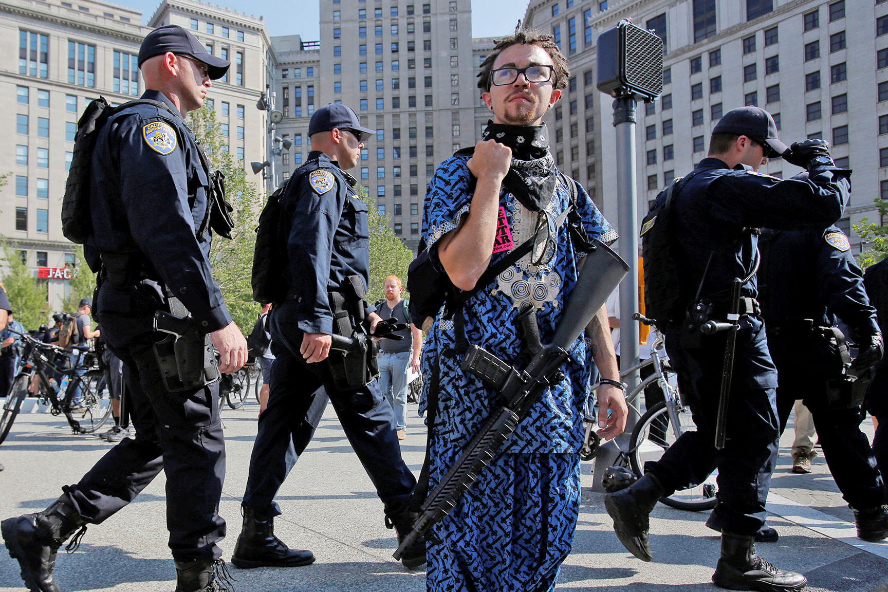 Jaimes Campbell, who advocates for open carry, stands with a gun as police walk by in Cleveland Public Square outside the Republican National Convention in Cleveland, Ohio