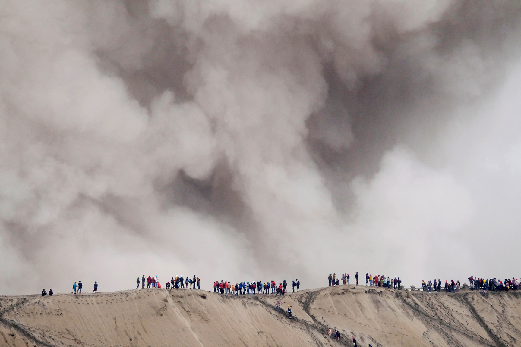 Mount Bromo spews ash as Hindu villagers and visitors stand on the edge of the volcanic crater ahead of Kasada ceremony in Probolinggo