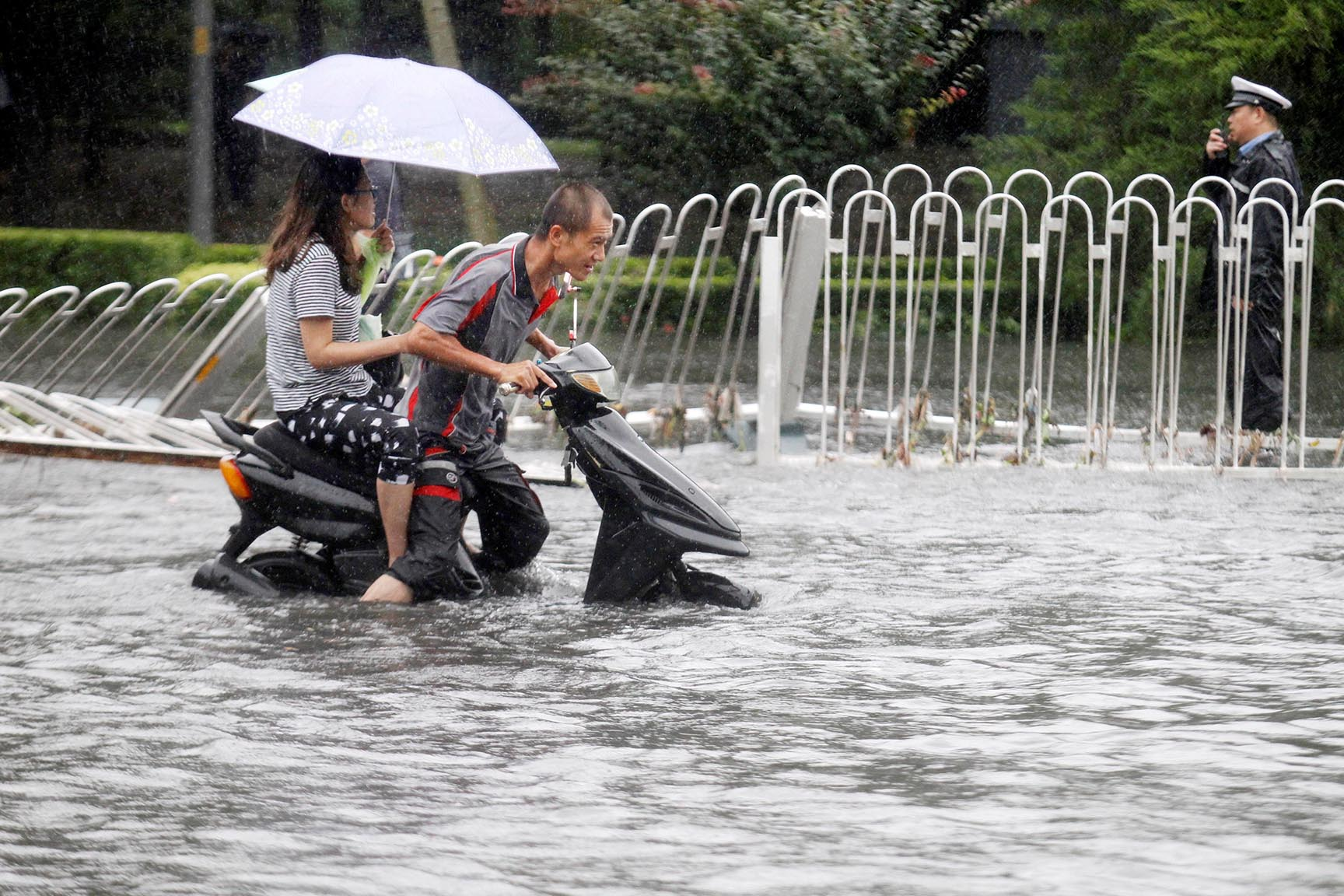 People ride along a flooded street during a heavy rainfall in Beijing