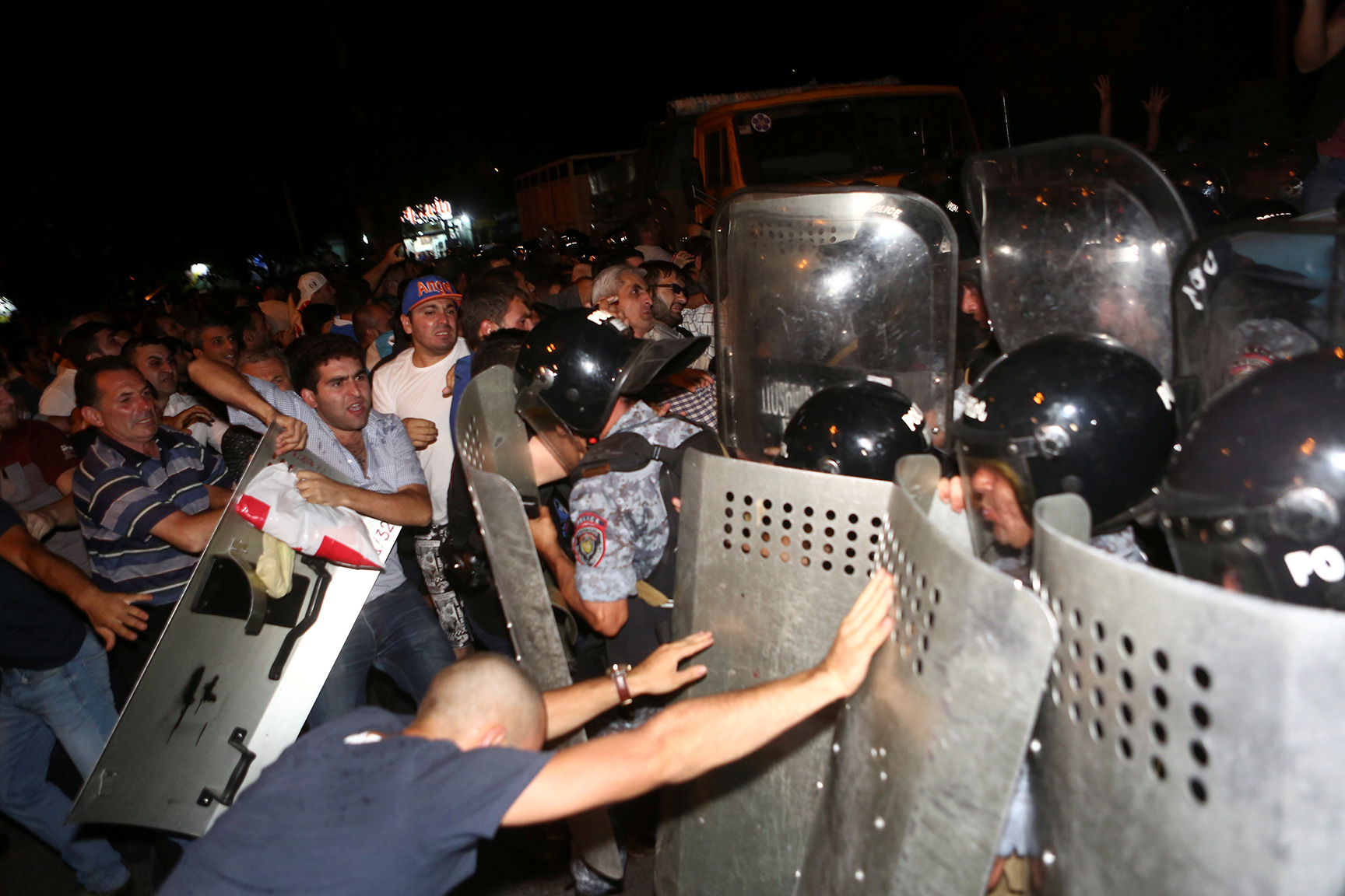 Riot police clash with demonstrators who had gathered in show of support for gunmen holding several hostages in police station in Yerevan