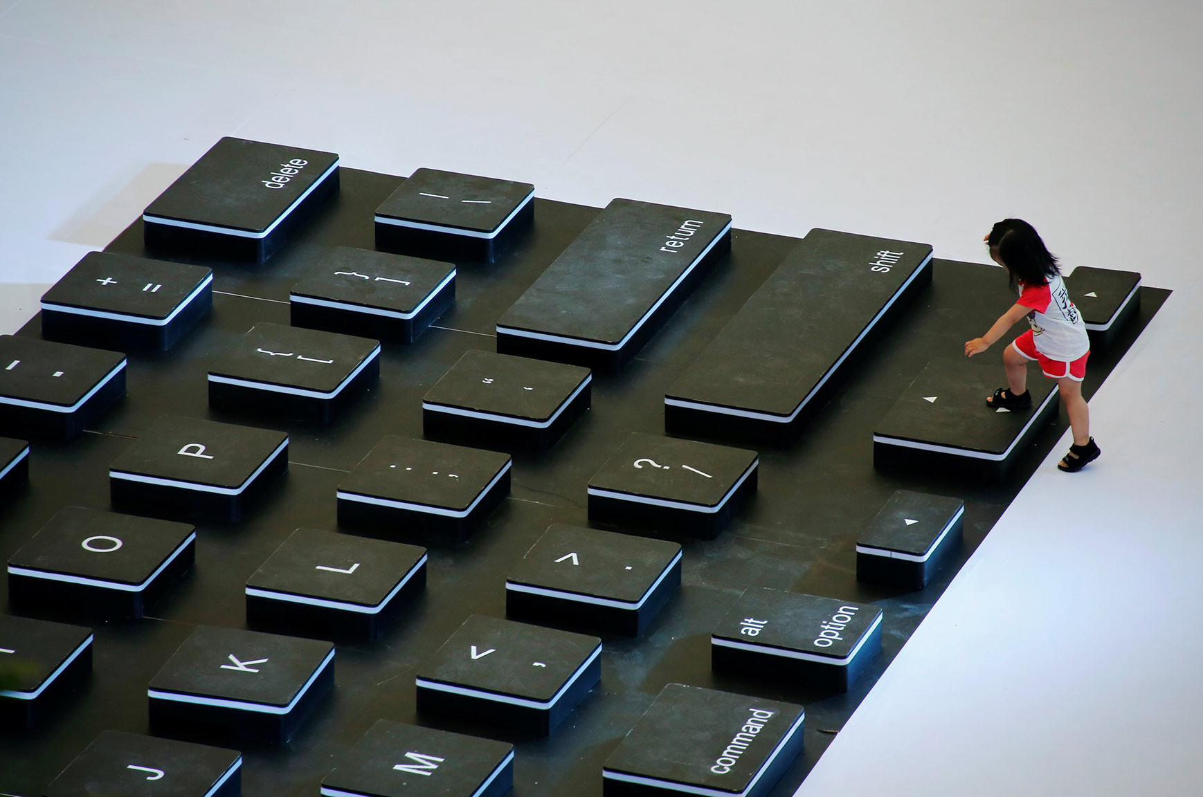 A child climbs onto a giant mockup laptop keyboard during a promotion event at a shopping centre in Beijing