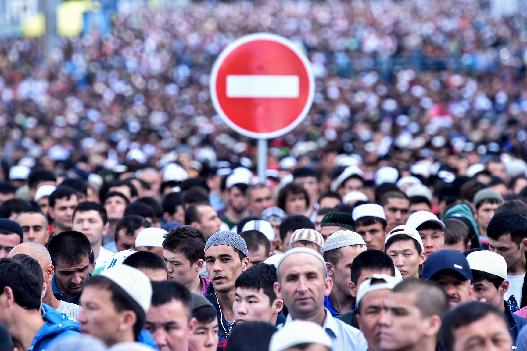 A traffic sign is seen behind Russian Muslims