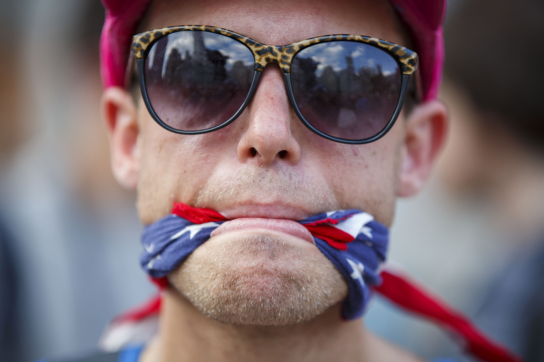 A protester stands with his mouth gagged