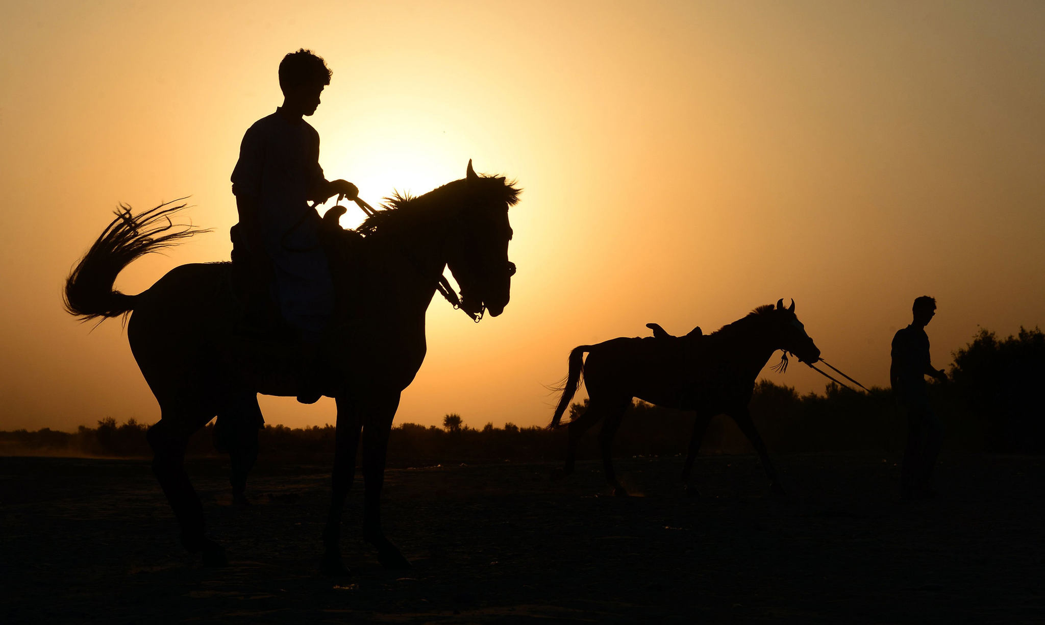 TOPSHOT - In this photograph taken on July 28, 2016, an Afghan man rides a horse as another one leads his horse as the sun sets in Injil district of Herat province. / AFP PHOTO / AREF KARIMIAREF KARIMI/AFP/Getty Images
