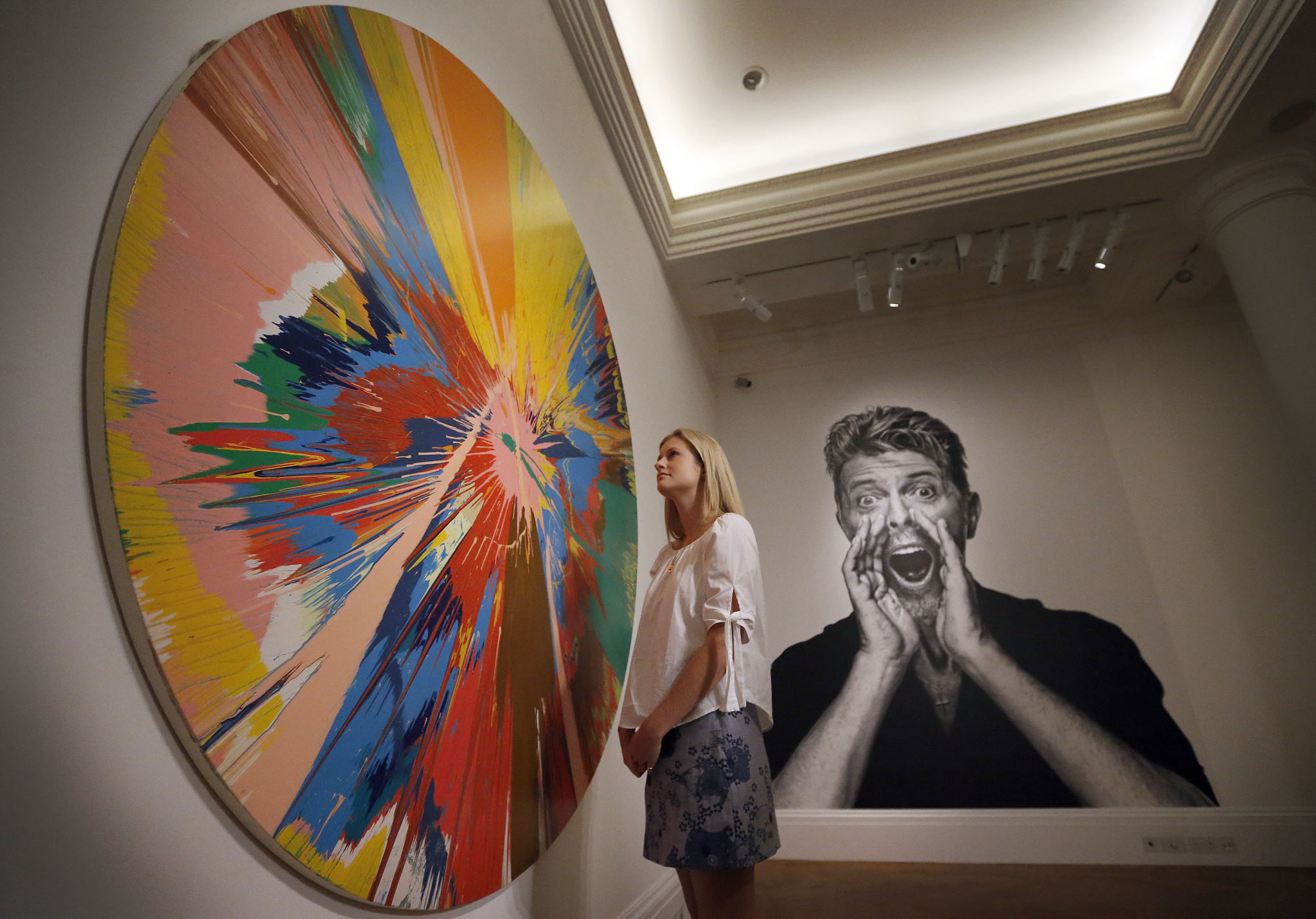 A woman looks at a painting by Damien Hirst in front of a portrait of David Bowie at Sotheby's in London.