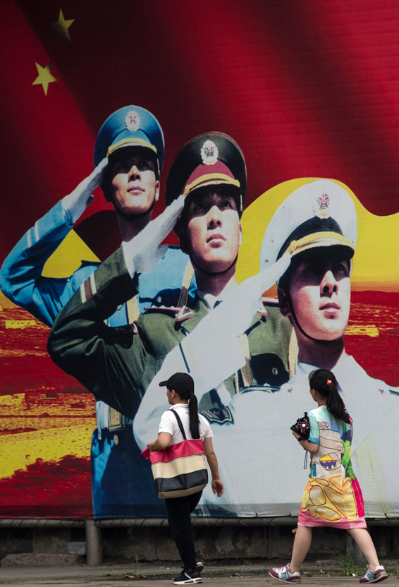 Pedestrians pass a military propaganda poster on a street in Shanghai on July 12, 2016.  Beijing braced on July 12 for an international tribunal's ruling on the South China Sea, where it has expansive territorial claims, with all eyes watching for the Asian giant's reaction on the ground or in the water. Beijing claims sovereignty over almost the whole of the South China Sea, on the basis of a segmented line that first appeared on Chinese maps in the 1940s, pitting it against several neighbours.