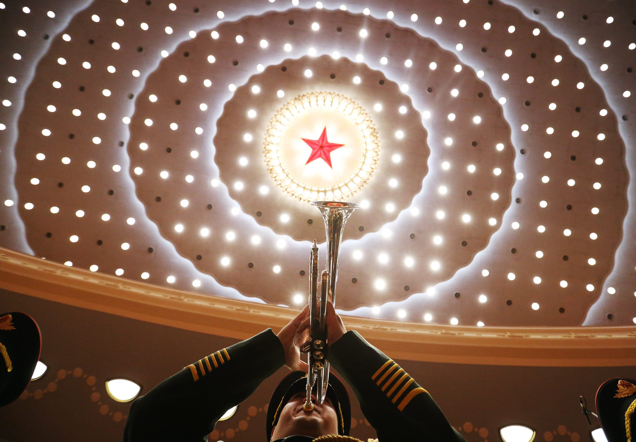 epaselect epa05400625 A Chinese military band member is seen playing his trumpet below the Communist Star before a celebration ceremony of the 95th anniversary of Founding the Communist Party of China at the Great Hall of the People (GHOP) in Beijing, China, 01 July 2016. China marks on 01 July the 95th anniversary of the formation of its ruling communist party with a grand ceremony at the GHOP.  EPA/HOW HWEE YOUNG
