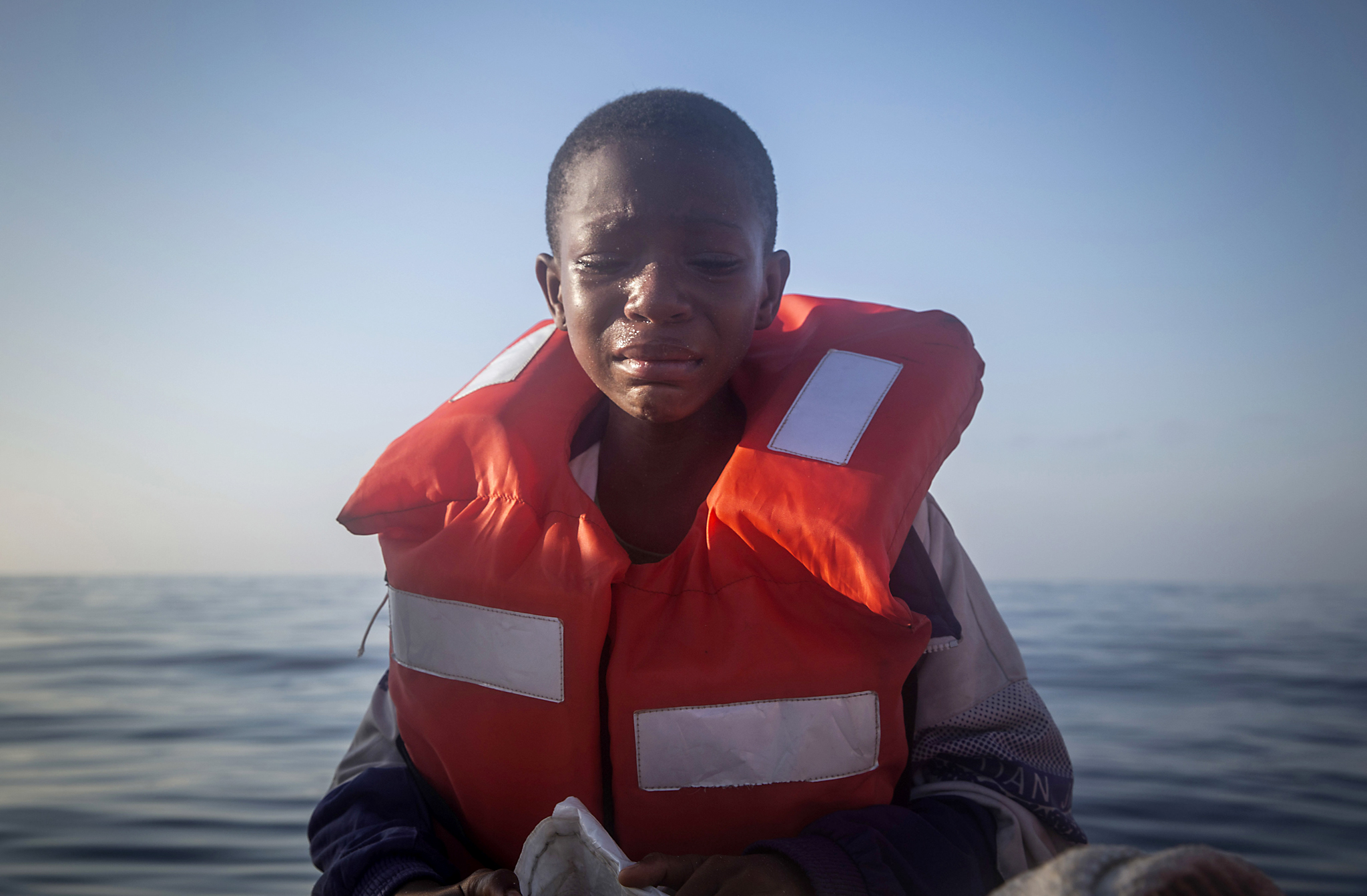 In this Thursday, July 28, 2016 photo, Dustin, 11, from Nigeria, who said his mother died in Libya, cries aboard a Spanish NGO's boat, after being rescued from an overcrowded rubber boat during a rescue operation on the Mediterranean Sea, about 23 kilometers (14 miles) north of Sabratha, Libya. (AP Photo/Santi Palacios)