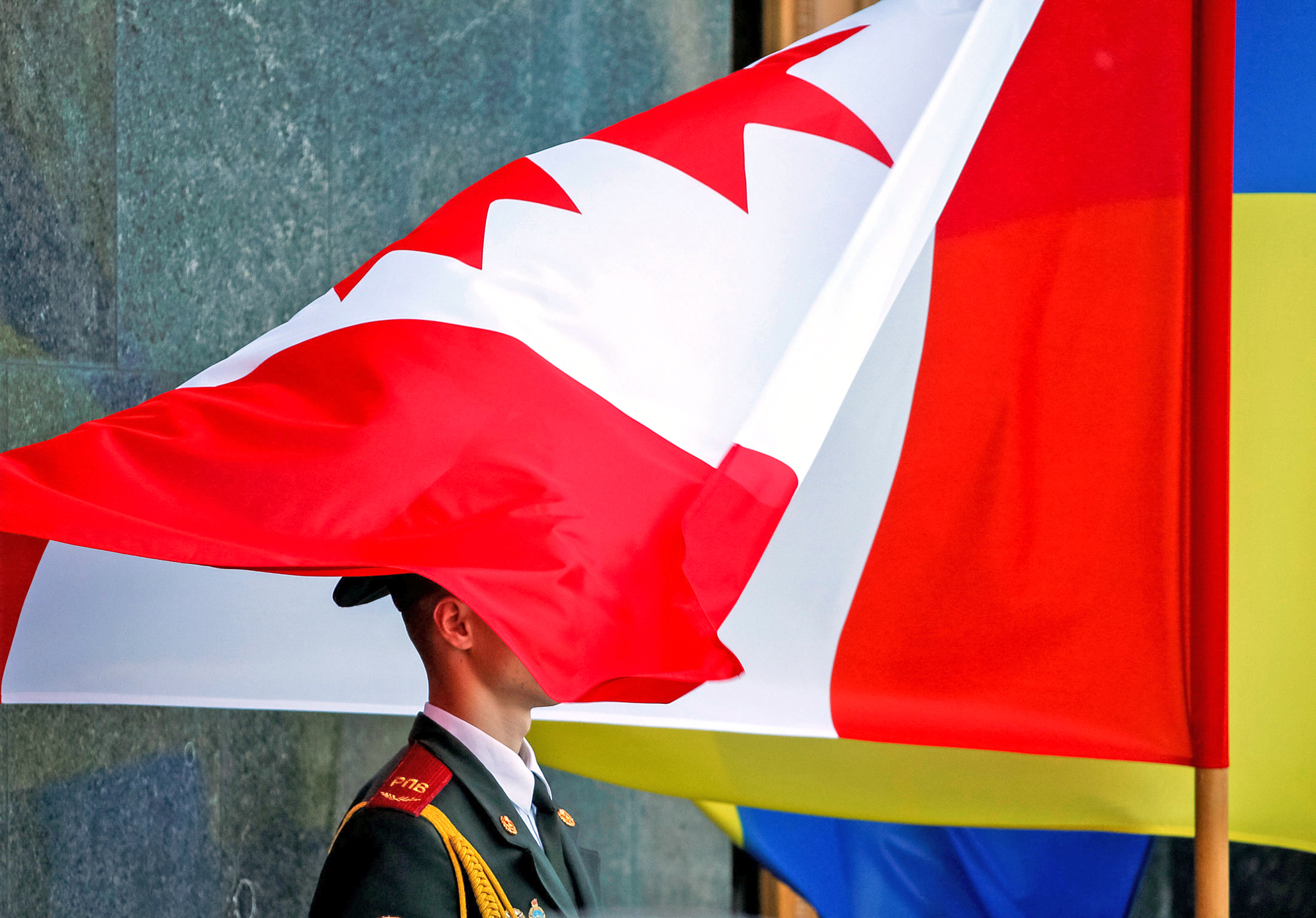 Canadian national flag covers a soldier from Ukraine's honour guards during a welcoming ceremony for Canada's Prime Minister Justin Trudeau in Kiev, Ukraine, July 11, 2016