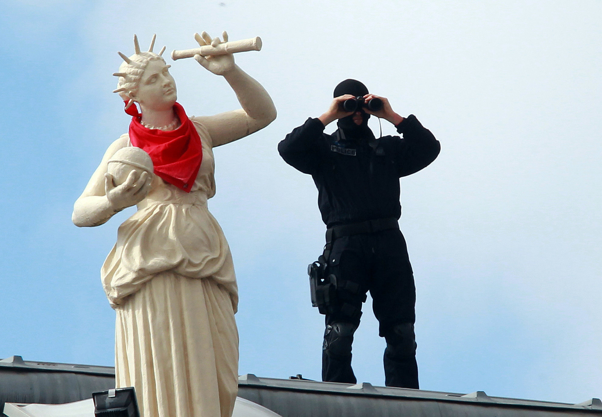 "In this photo taken on Wednesday, July 27, 2016, a French police officers watches the festivities through binoculars on the roof of the town hall, during the opening night of the Bayonne festival, or ""Fetes de Bayonne"", in Bayonne, southwestern France.  Bayonne, the cultural capital of the French Basque country, hosts the yearly traditional Bayonne festival from July 27-31, and is expected to attract about one million people this year from all over France, Spain, and other European countries. (AP Photo/Bob Edme)"