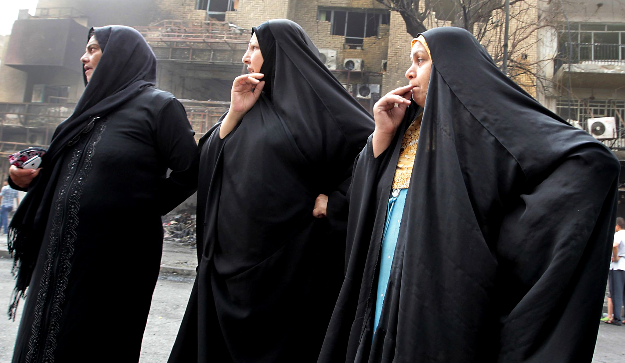 Iraqis react as they visit the aftermath of a massive bombing in Baghdad's Karrada neighbourhood on July 4, 2016.  Iraqis mourned the more than 200 people killed by a jihadist-claimed suicide car bombing that was among the deadliest ever attacks in the country. The blast, which the Islamic State group said it carried out, hit the Karrada district early on July 3 as the area was packed with shoppers ahead of this week's holiday marking the end of the Muslim fasting month of Ramadan.   / AFP PHOTO / SABAH ARARSABAH ARAR/AFP/Getty Images