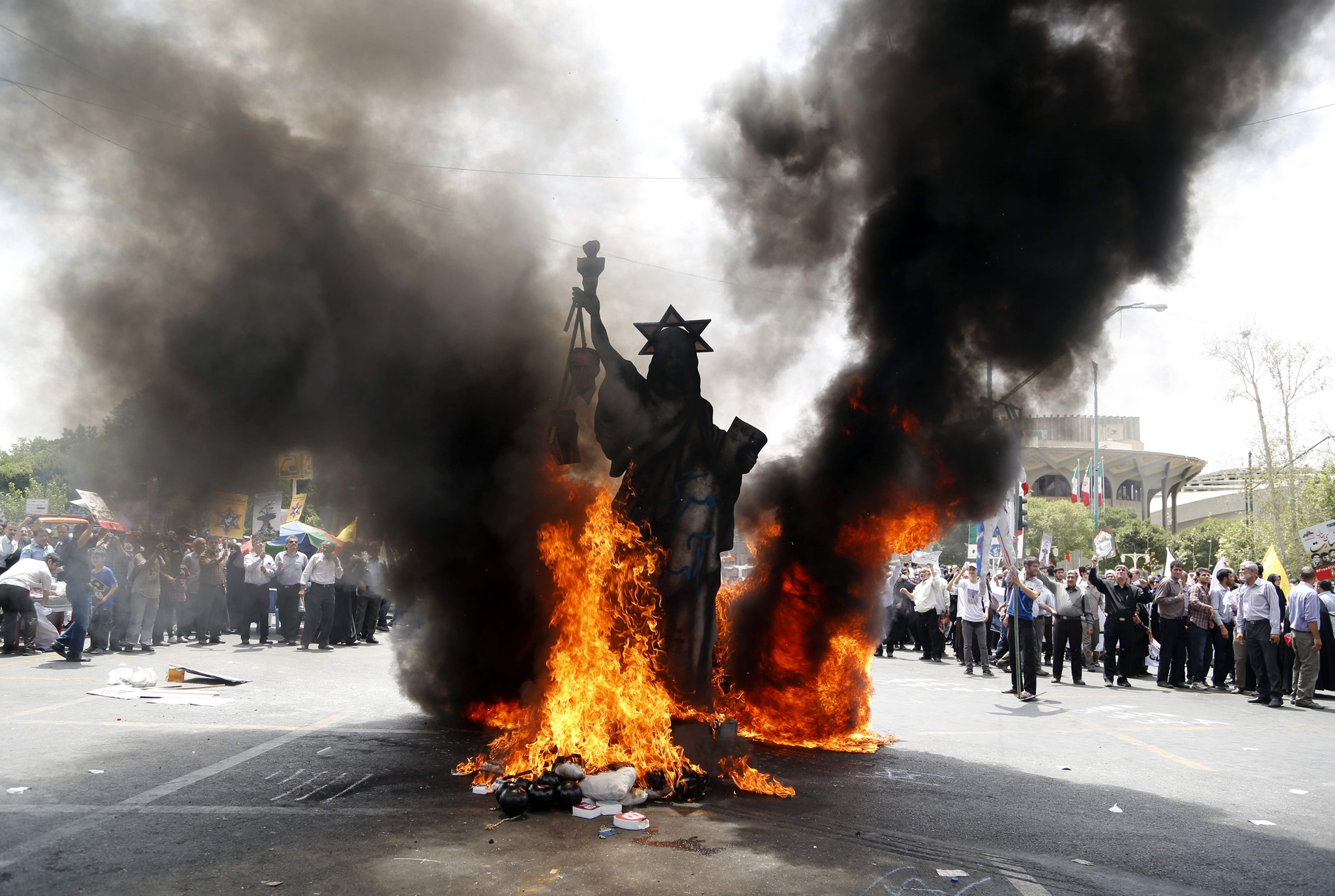 TOPSHOT - A statue depicting US' Statue of Liberty decorated with a Star of David on its head is set ablaze by Iranian protestors during a parade marking al-Quds (Jerusalem) Day in Tehran on July 1, 2016. Tens of thousands joined pro-Palestinian rallies in Tehran, as the annual Quds Day protests take on broader meaning for a region mired in bitter disputes and war.    / AFP PHOTO / ATTA KENAREATTA KENARE/AFP/Getty Images