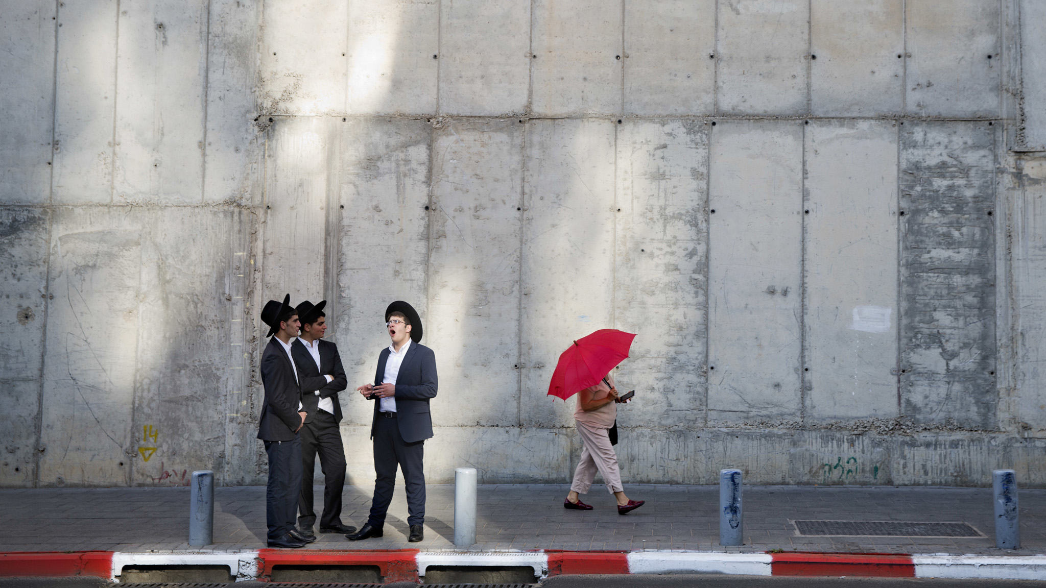 A woman shades herself with an umbrella next to a group of Ultra-Orthodox Jewish men as they wait for transportation at a bus stop in Bnei Brak, Israel, Monday, July 11, 2016. (AP Photo/Oded Balilty)