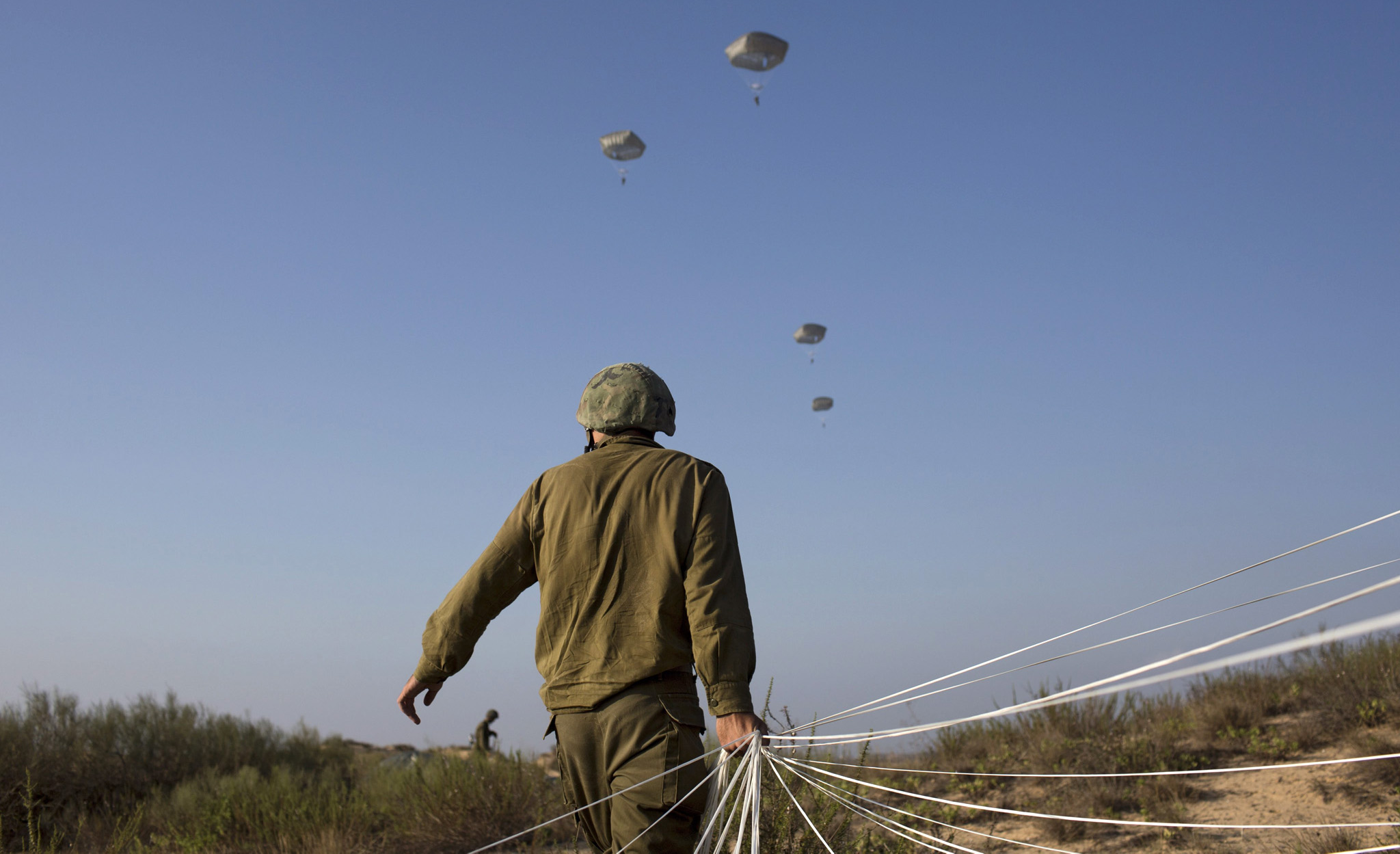 epa05408287 Israeli army paratroopers take part in a training jump in full battle gear over the Palmachim military base near Tel Aviv, Israel, 05 July 2016. Although the Paratroopers Brigade has had only one operational combat parachute drop ever, during the 1956 Sinai War, volunteers accepted into the elite unit undergo operational training jumps with all the equipment needed for battle.  EPA/ABIR SULTAN