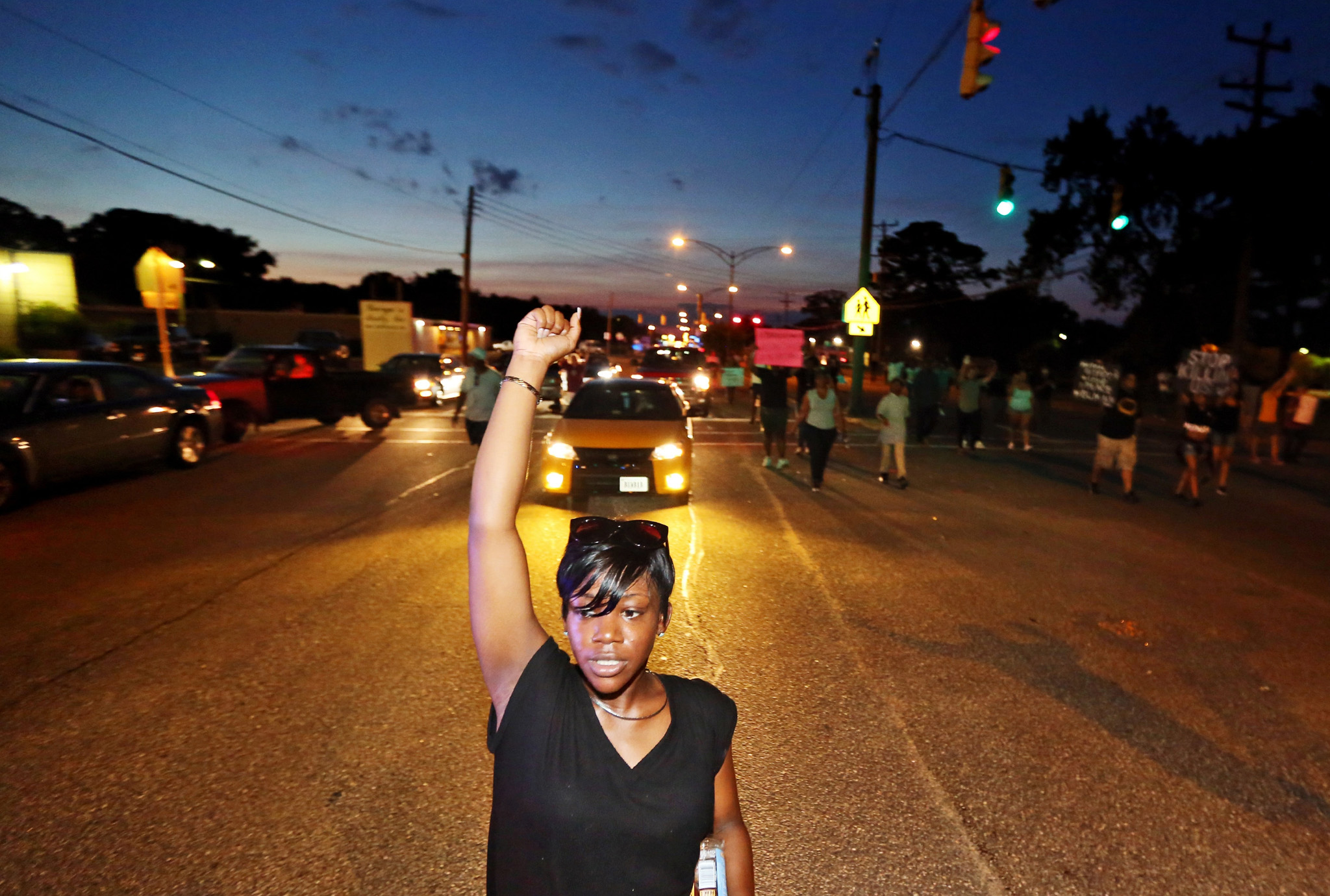 Sirica Bolling raises her fist as she walks down Jefferson Avenue during a Black Lives Matter protest against police brutality in Newport News, Va., Sunday July 10, 2016. (Aileen Devlin/The Daily Press via AP)