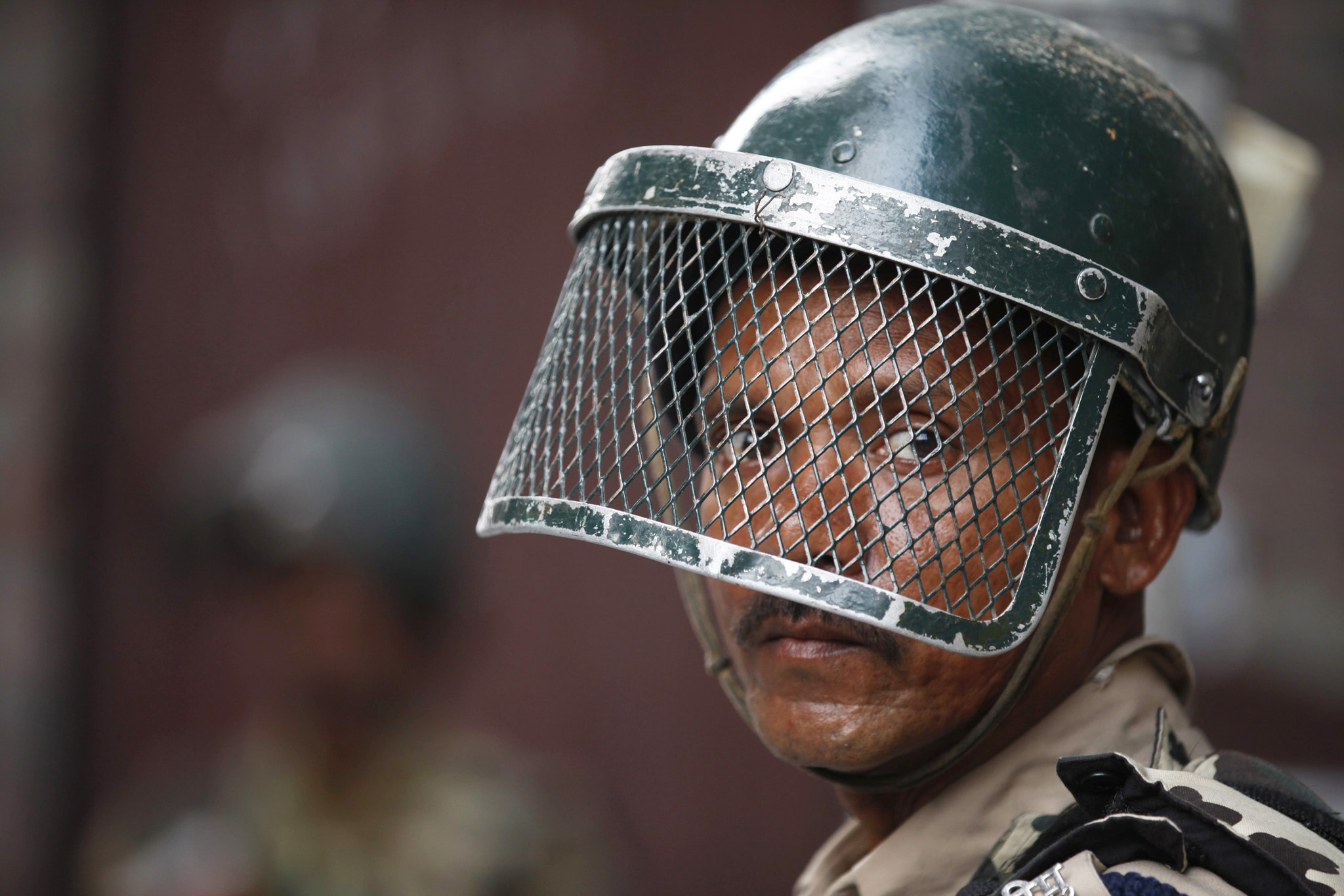 epa05422636 An Indian paramilitary officer stands guard during a curfew in Srinagar, the summer capital of Indian Kashmir, 13 July 2016. The authorities imposed curfew and severe restrictions in most parts of Kashmir valley for the fifth consecutive day to contain protests following the killing of militant commander Burhan Muzaffar Wani. According to local news reports the death toll reached 32 and over 1,300 persons were injured across Indian Kashmir during clashes over the past six days.  EPA/FAROOQ KHAN