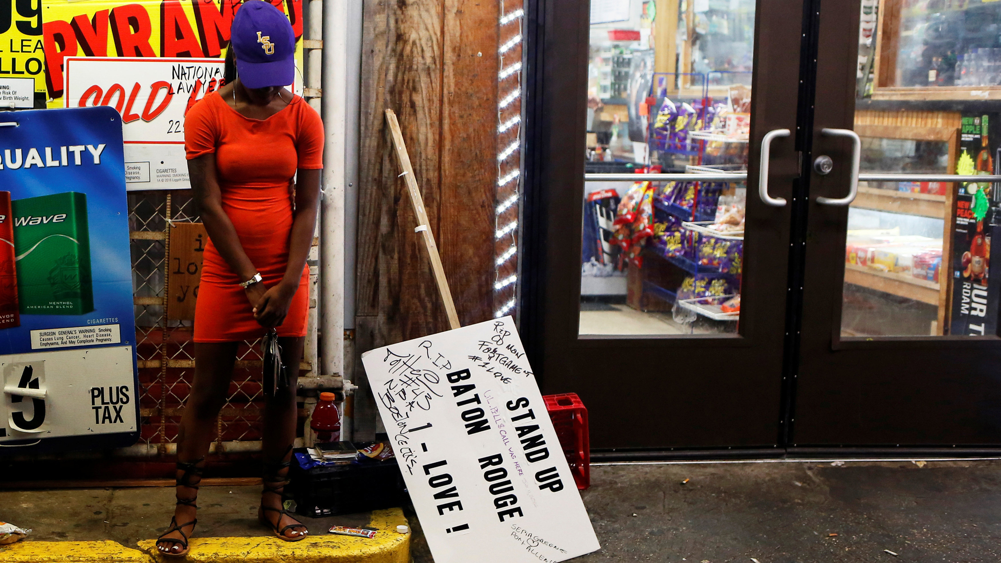A woman stands by a makeshift memorial at the Triple S convenience store where Alton Sterling was shot dead by police in Baton Rouge, Louisiana, U.S., July 11, 2016. REUTERS/Shannon Stapleton