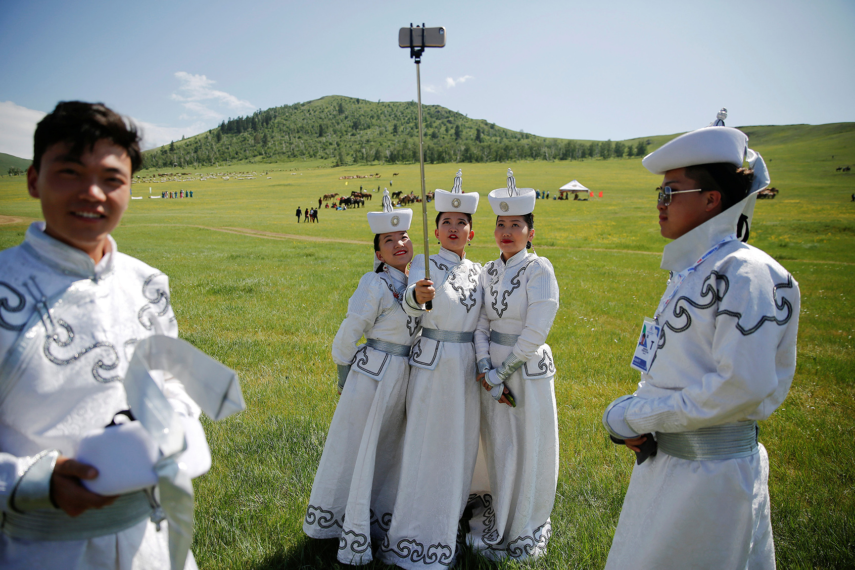Performers wearing traditional clothes take pictures of themselves as they wait for delegations to arrive for traditional nomadic Naadam festival performance during the Asia-Europe Meeting (ASEM) summit just outside Ulaanbaatar