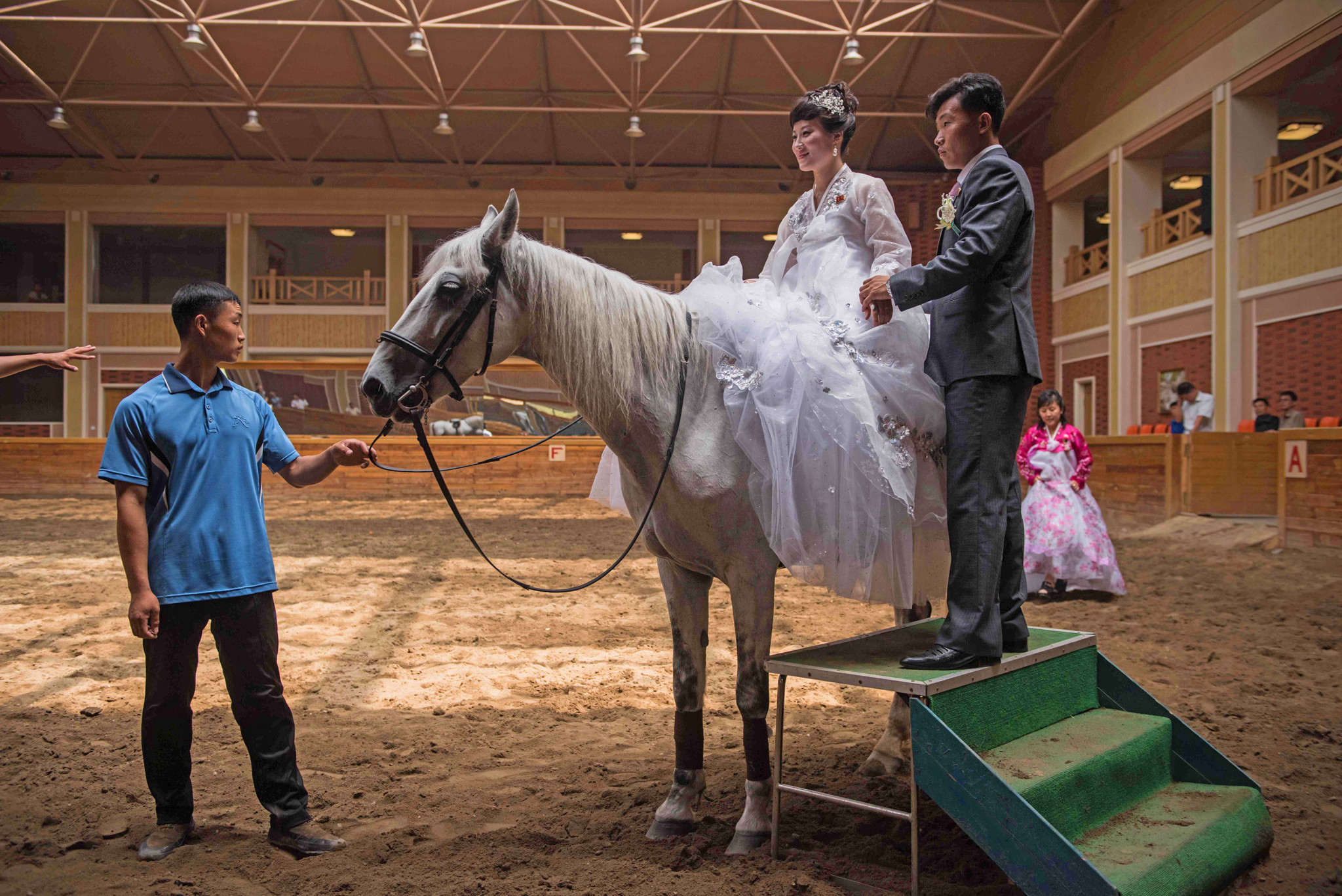 A bride and groom pose for photos with a horse at the Mirim riding school on the outskirts of Pyongyang on July 12, 2016