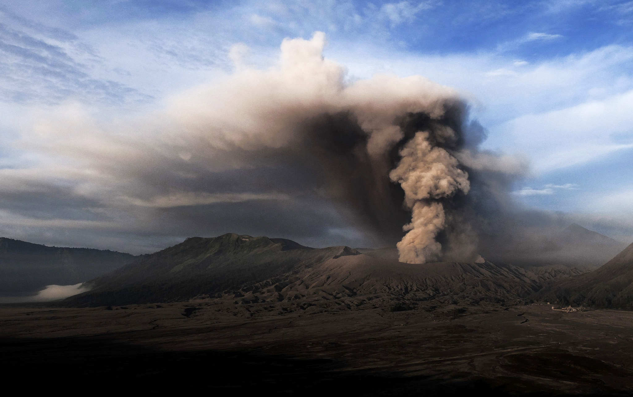 TOPSHOT - In this photo taken from Probolinggo in Indonesia's East Java province, Mount Bromo spews ashes into the air during a volcanic eruption on July 13, 2016. The volcano spewed a column of ash by up to 1,200 meters into the sky and forced the closing all activities at the nearby Abdurrahman Saleh airport in Malang district, according to local reports stating the national disaster management agency. Bromo lies within Bromo-Tengger-Semeru National Park, a huge caldera containing several volcanoes. / AFP PHOTO / BAY ISMOYOBAY ISMOYO/AFP/Getty Images