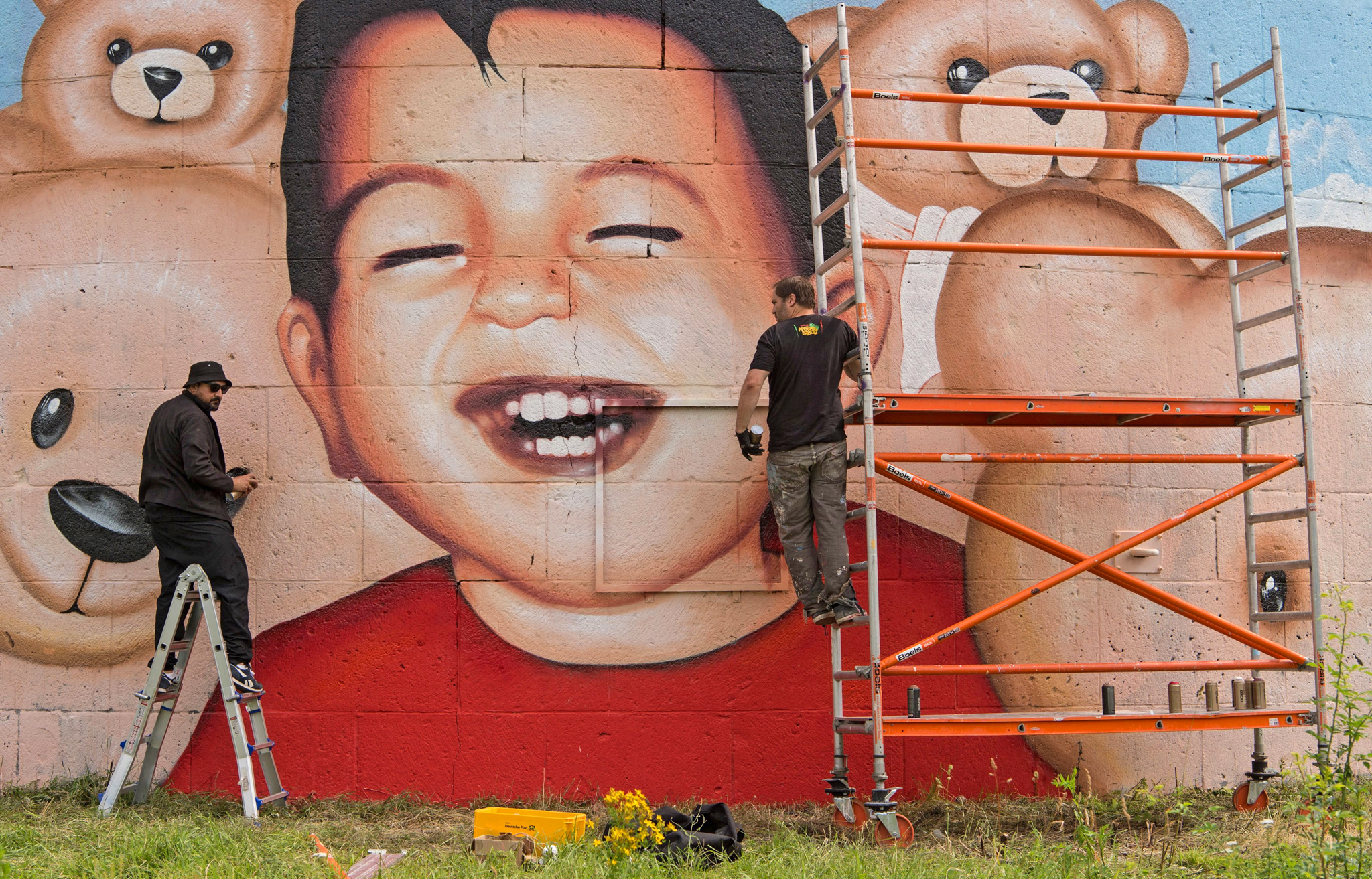 epa05406928 Graffiti artists Oguz Sen (L) and Justus Becker (R) make the finishing touches to a new mural of drowned refugee Aylan Kurdi, at Osthafen in Frankfurt Main, Germany, 04 July 2016. After the previous picture was daubed with slogans, the new image shows a living, laughing Aylan surrounded by stuffed toys.