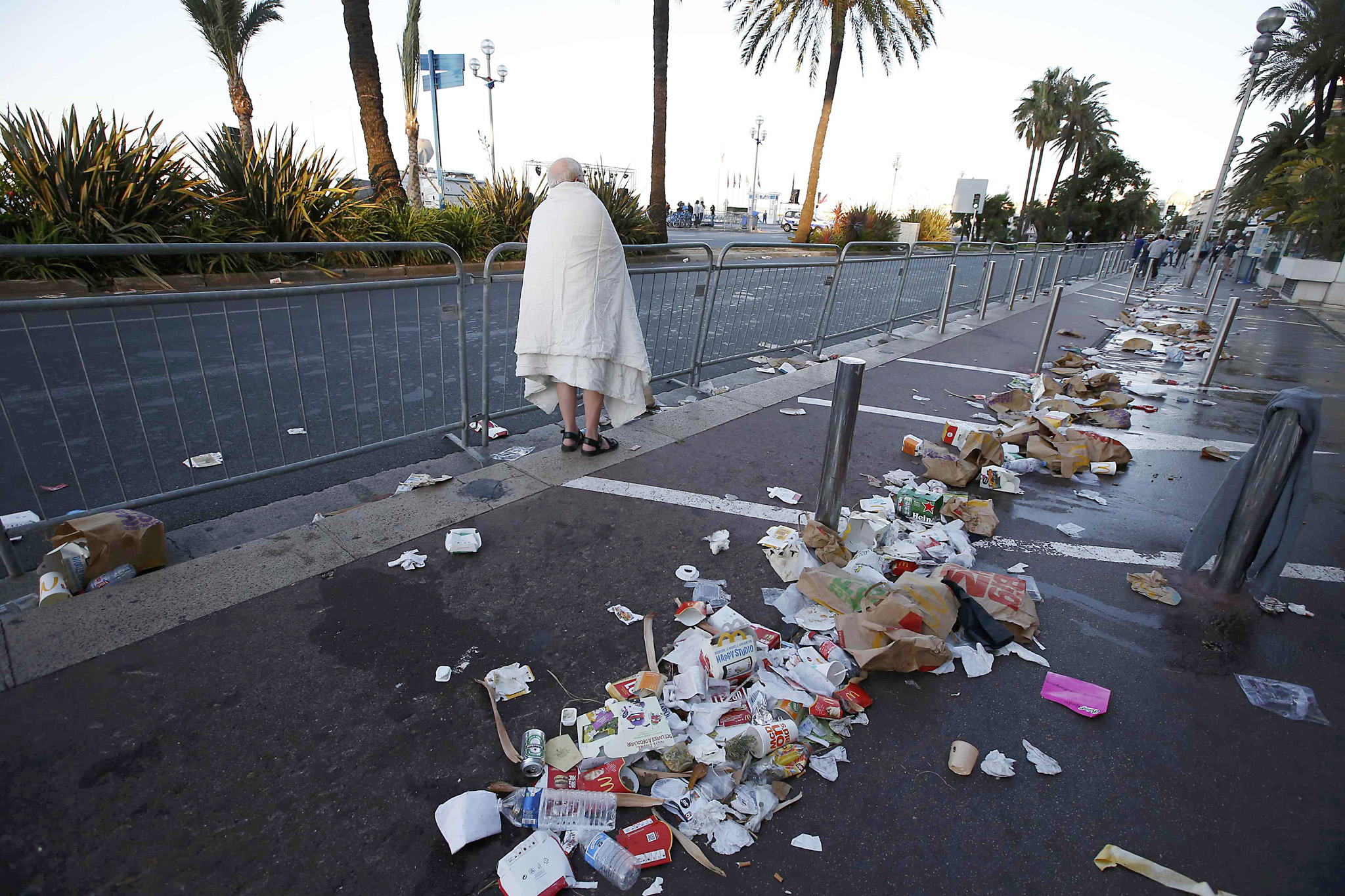 A man walks through debris scatterd on the street the day after a truck ran into a crowd at high speed killing scores celebrating the Bastille Day July 14 national holiday on the Promenade des Anglais in Nice, France, July 15, 2016.      REUTERS/Eric Gaillard