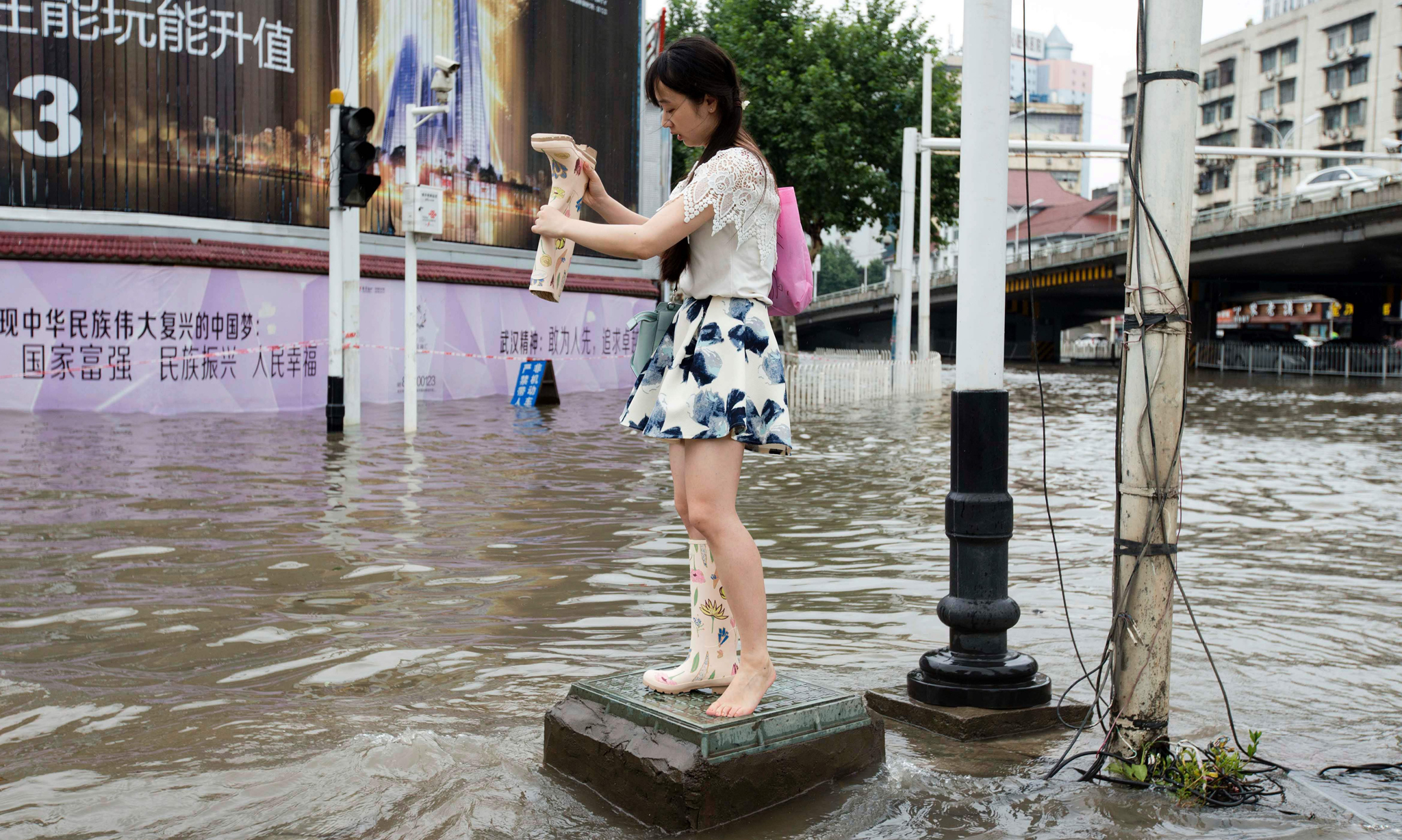 This picture taken on July 6, 2016 shows a woman emptying the water from her boots at a flooded area in Wuhan, central China's Hubei province