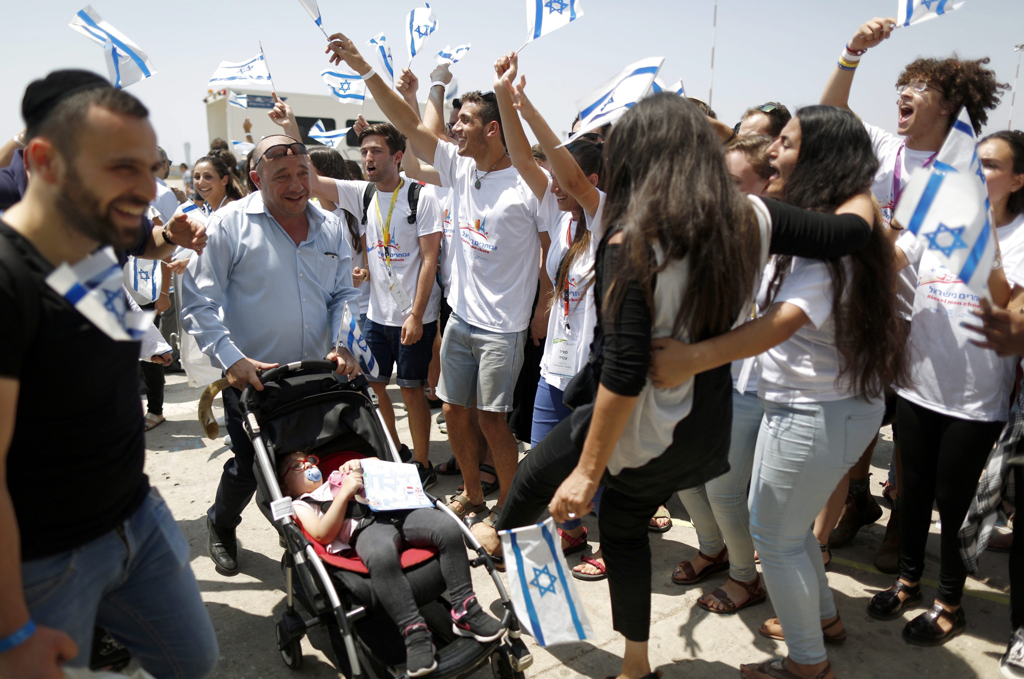 sraelis wave national flags as they welcome newly-arrived Jewish immigrants from France at Ben Gurion Airport, in Lod, near Tel Aviv, Israel,