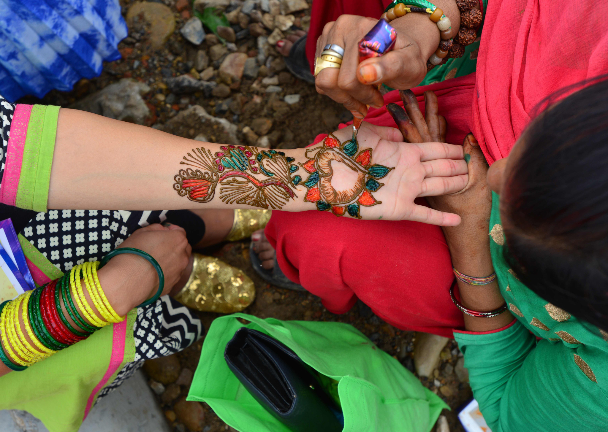 An artist decorates the hand of a Nepalese devotee with mehendi (henna) during Shravan festivities in Kathmandu