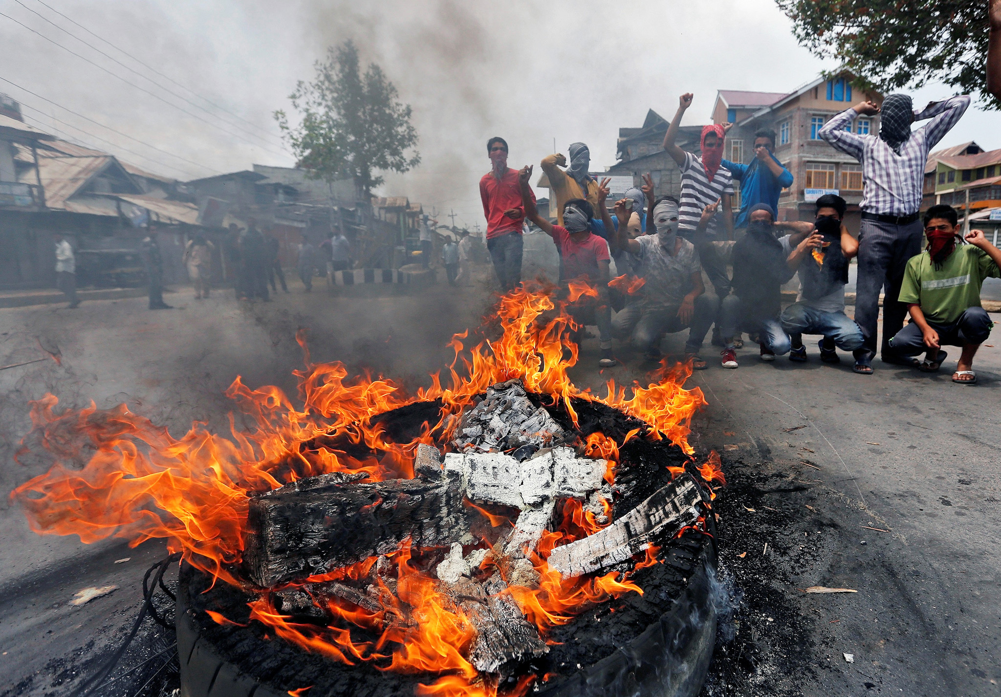 Masked demonstrators shout slogans next to a burning tyre during a protest in Srinagar against the recent killings in Kashmir