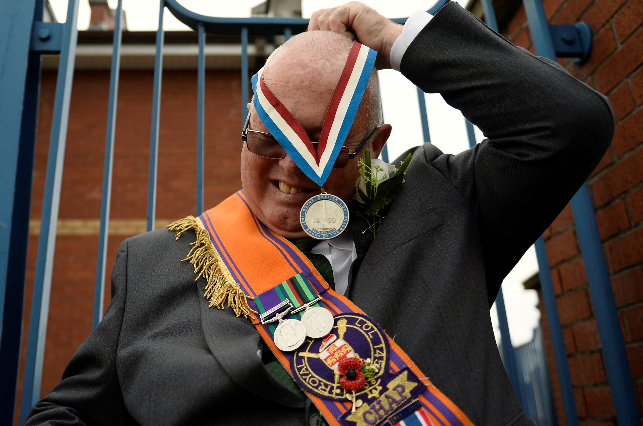 A member of the Twelfth of July Orange Order parade is seen putting on a medal during a march through Crumlin Road in Belfast, Northern Ireland