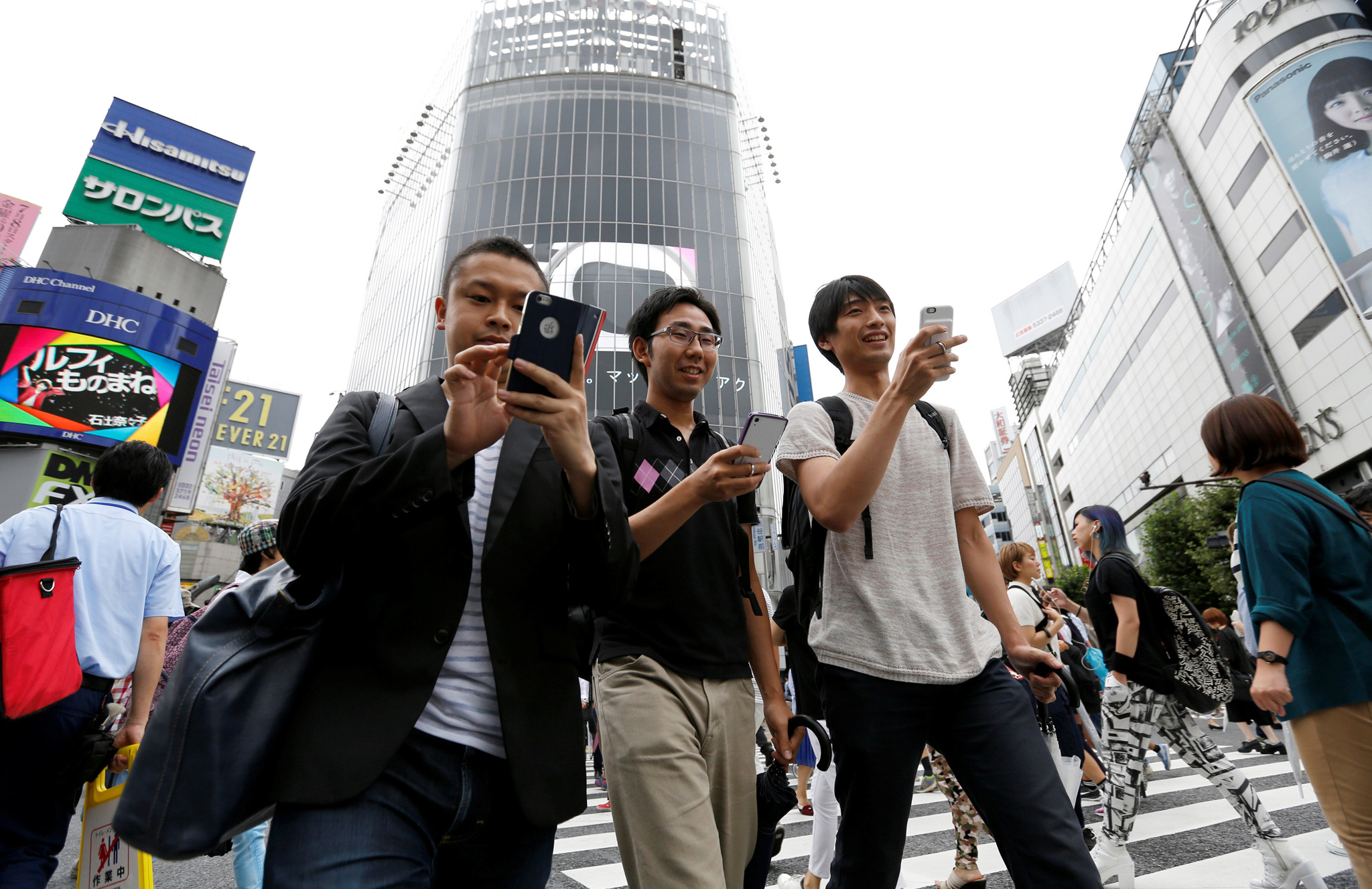 "Men play the augmented reality mobile game ""Pokemon Go"" by Nintendo on their mobile phones as they walk at a busy crossing in Shibuya district in Tokyo, Japan"