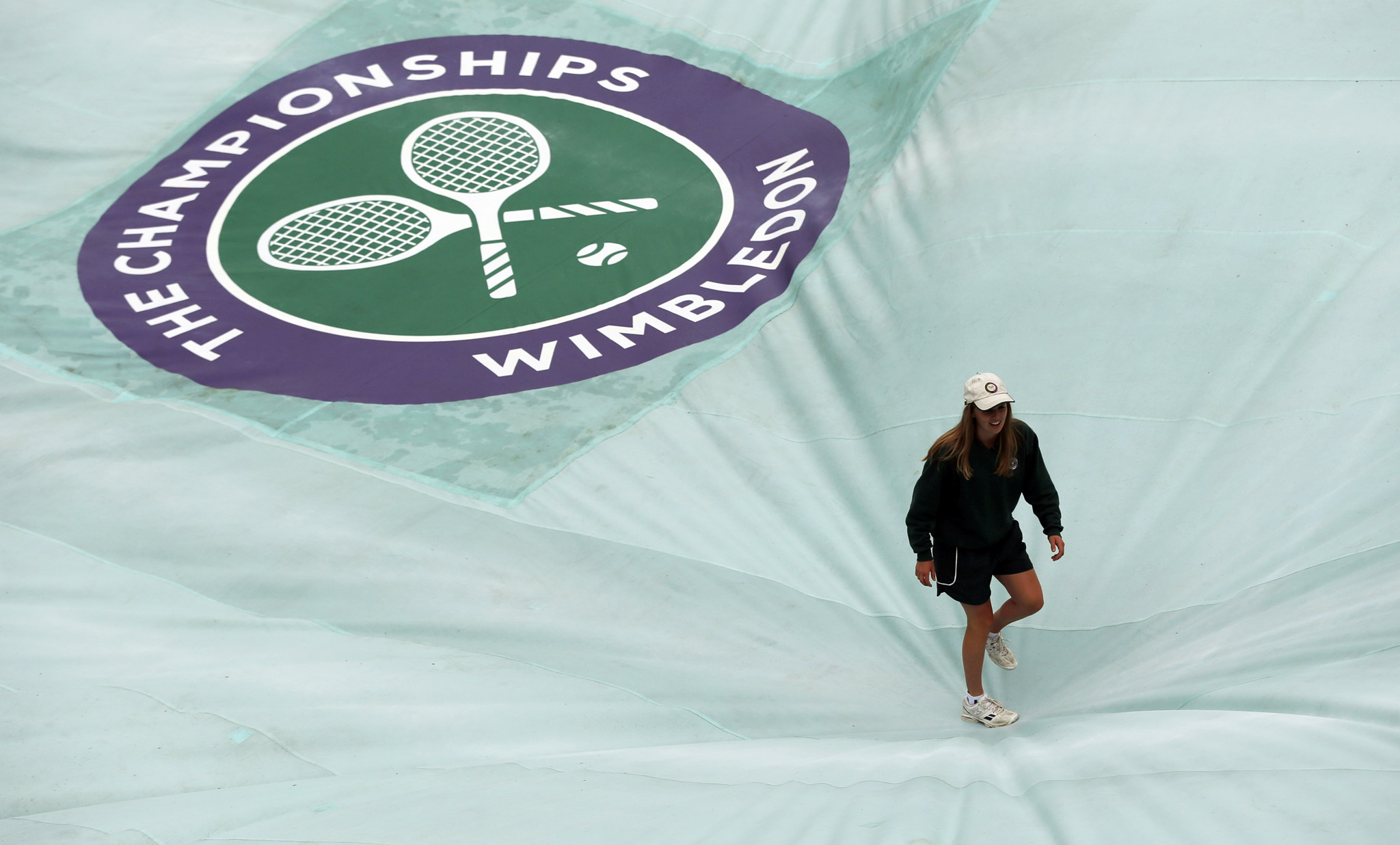 A member of the ground staff walks on the court cover, as rain delays play on day five of the Wimbledon Tennis Championships in London, Friday, July 1, 2016. (AP Photo/Ben Curtis)