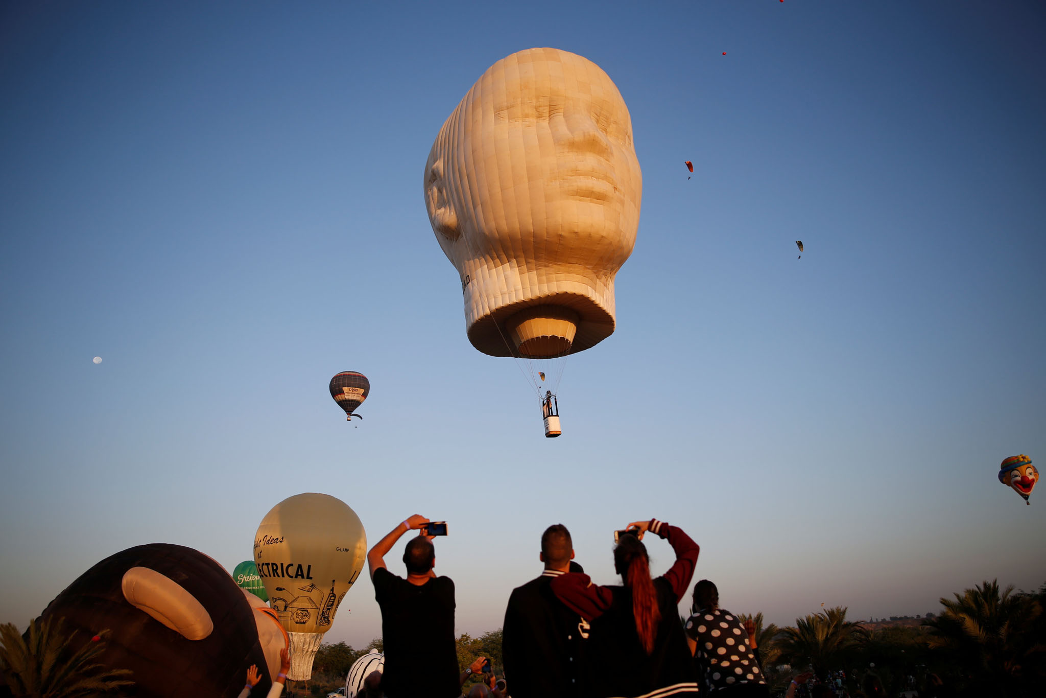 People are seen watching hot air balloons fly overhead during a two-day international hot air balloon festival in Eshkol Park near the southern city of Netivot, Israel