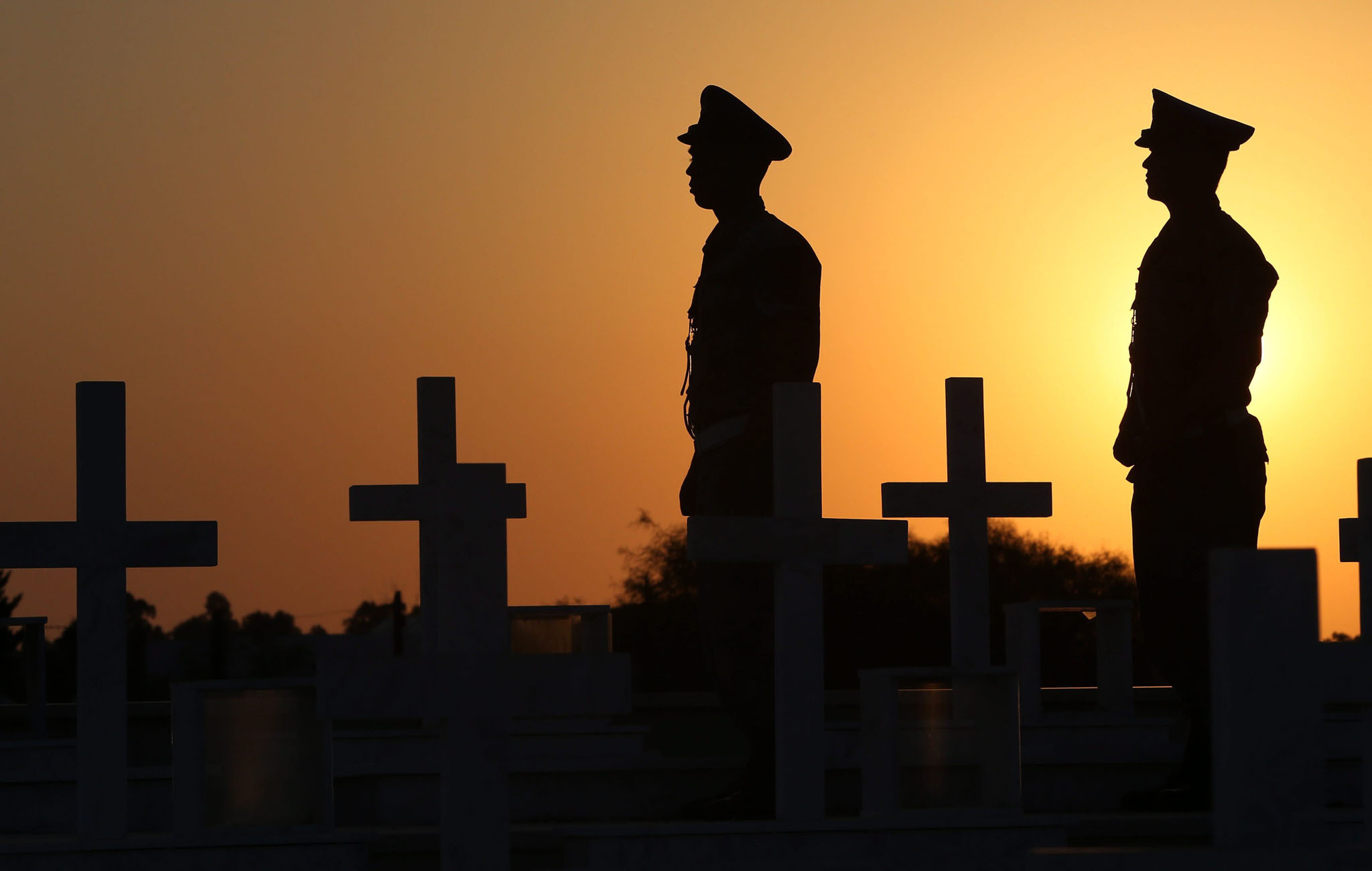 Cypriot soldiers are silhouetted with the crosses marking the graves of Greek and Cypriot soldiers killed in the 1974 Turkish invasion of Cyprus, at the Tymvos Macedonitissas military cemetery in Nicosia, Cyprus,