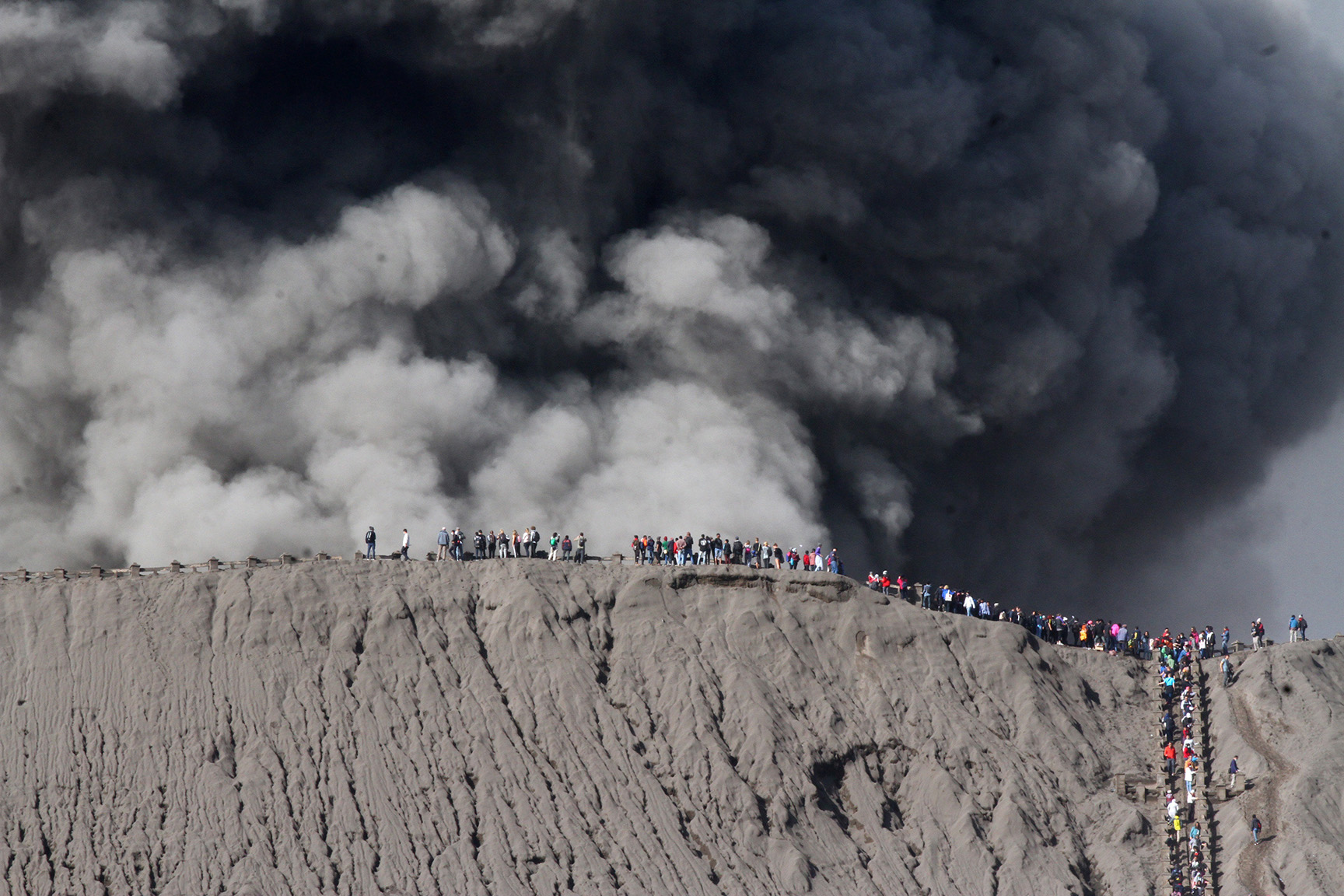 People standing on the edge of the crater while watching the eruption of Mount Bromo in Probolinggo