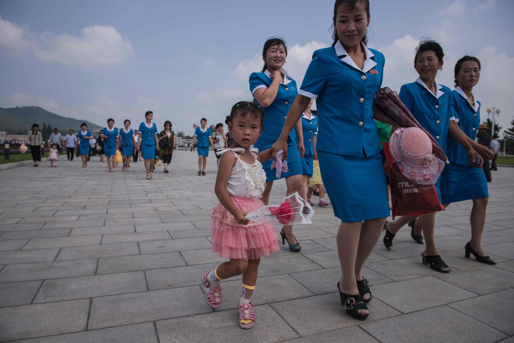 A group of North Korean workers and a child walk to pay their respects to late North Korean leader Kim Il-Sung on the anniversary of his death, outside the Kumsusan Palace of the Sun mausoleum in Pyongyang