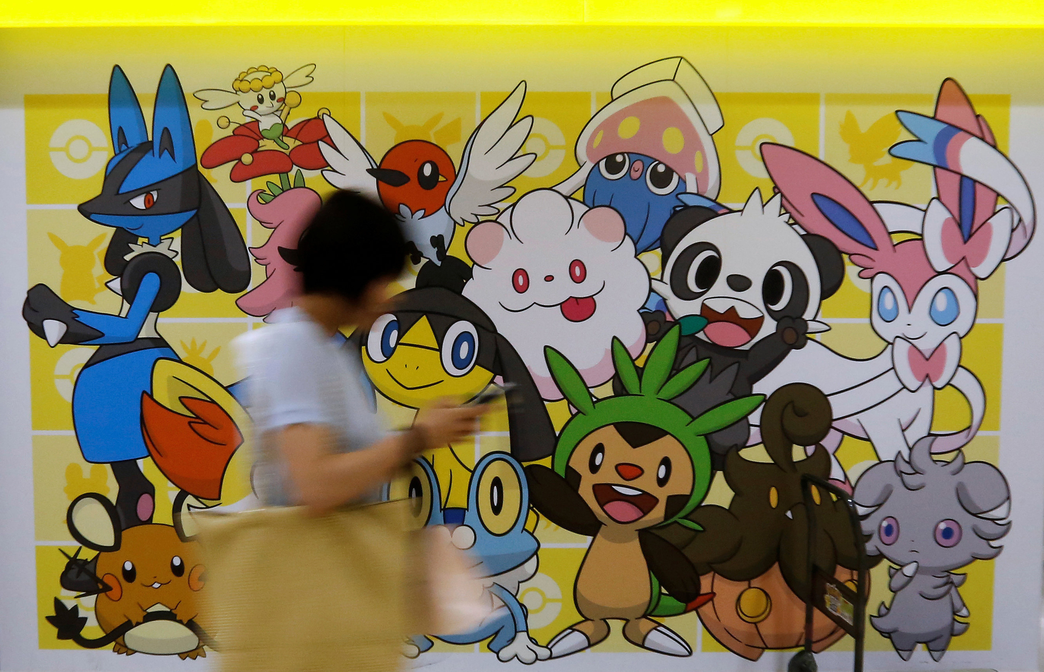 A woman using a mobile phone walks past a shop selling Pokemon goods in Tokyo, Japan