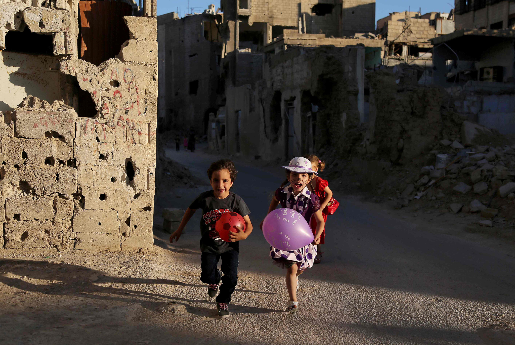 Syrian children run amidst heavily damaged buildings during an activity organised by a charity group in Jobar, a rebel-held district on the eastern outskirts of the capital Damascus