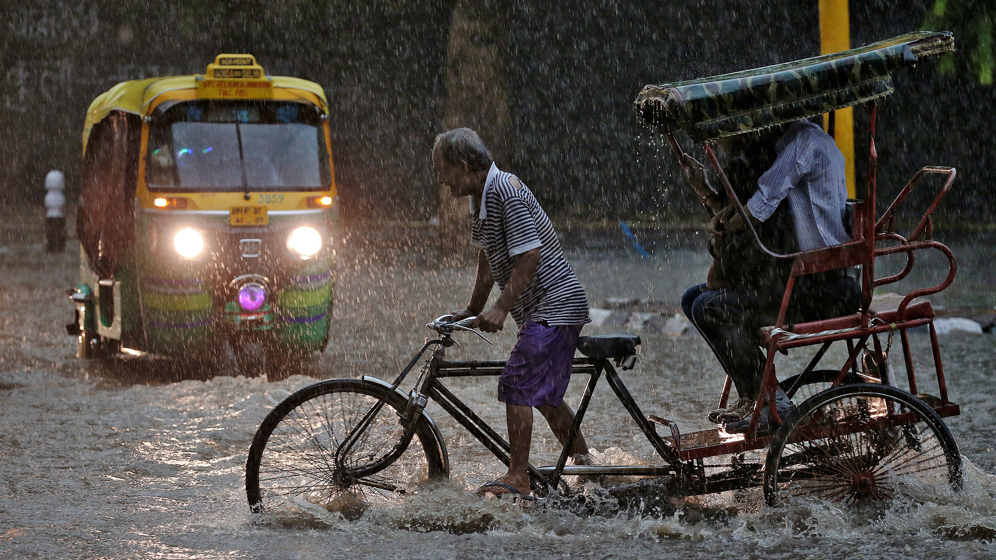 A man pedals his cycle rickshaw during monsoon rains in New Delhi