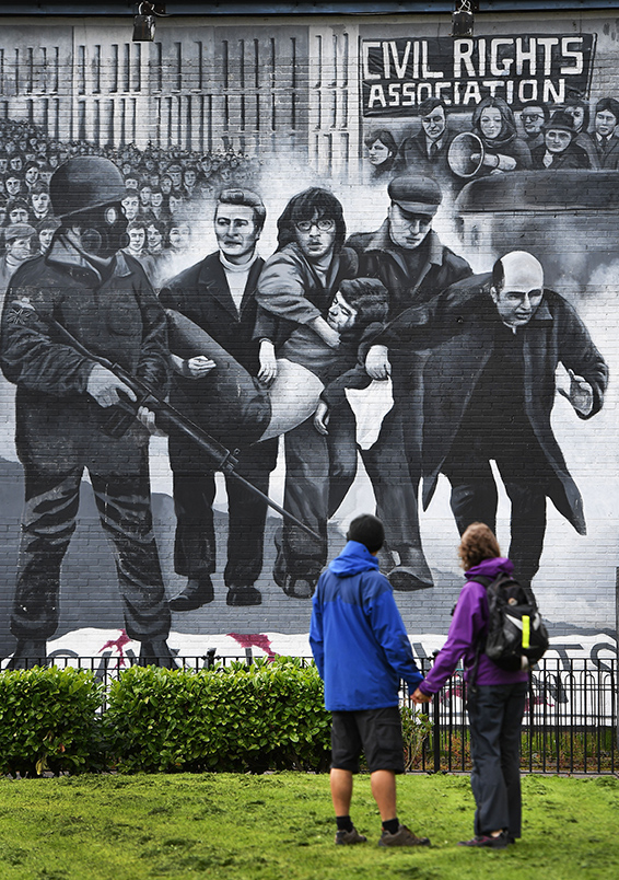 A couple look at the mural on Free Derry Corner depicting an image of Bishop Daly as parishioners and well wishers pay their respects to the late retired Bishop of Derry, Dr. Edward Daly as he lies in state at St. Eugene's Cathedral on August 9, 2016 in Londonderry, Northern Ireland. The iconic image of the then Fr Daly waving a handkerchief over one of the Bloody Sunday victims became one of the most enduring images of the Troubles in Northern Ireland. Bishop Daly who has been described as a fearless peace-builder passed away at the age of 82 following a brief illness.