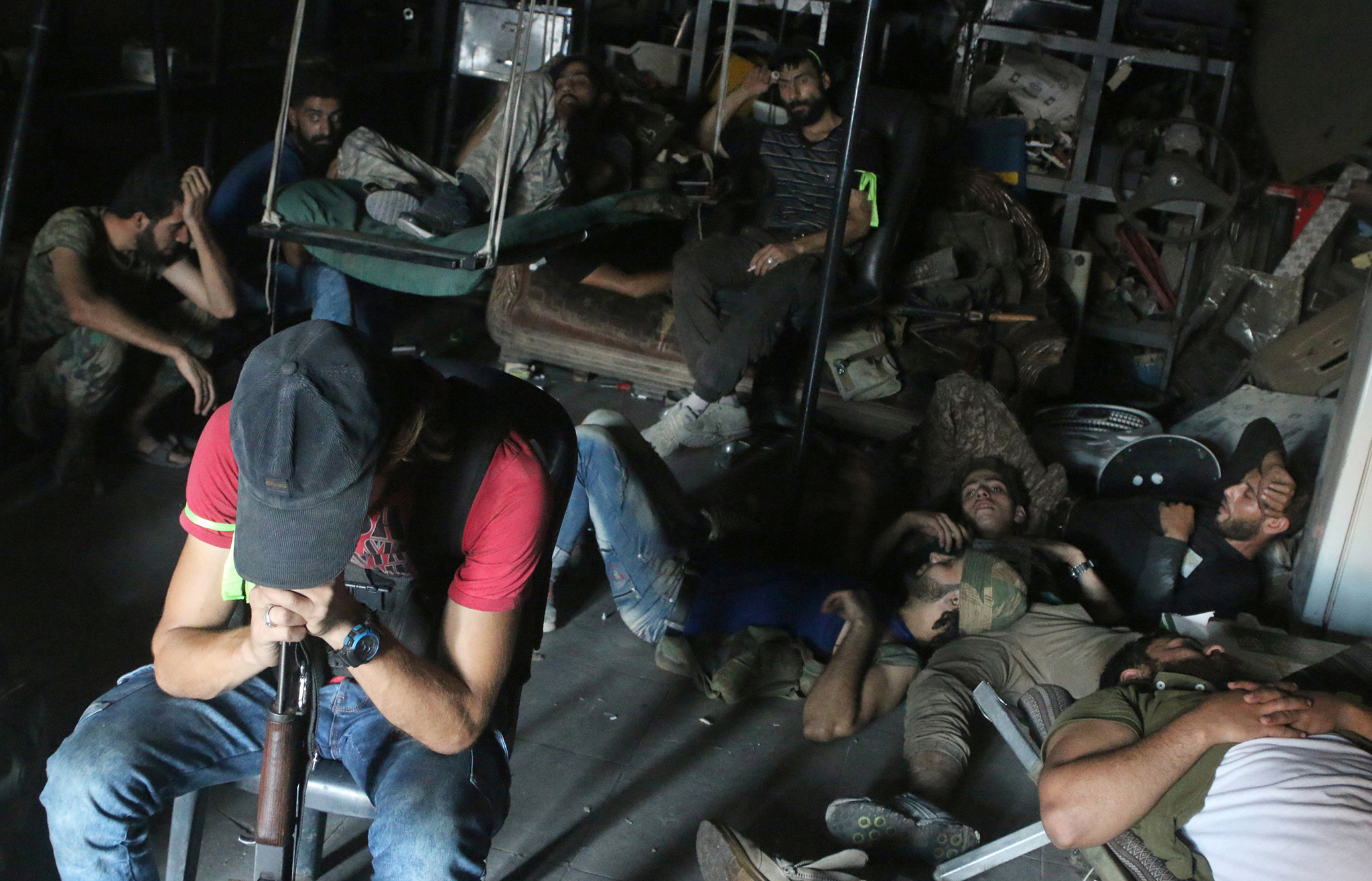 Free Syrian Army fighters rest inside a mechanic shop in Ramousah area southwest of Aleppo, Syria