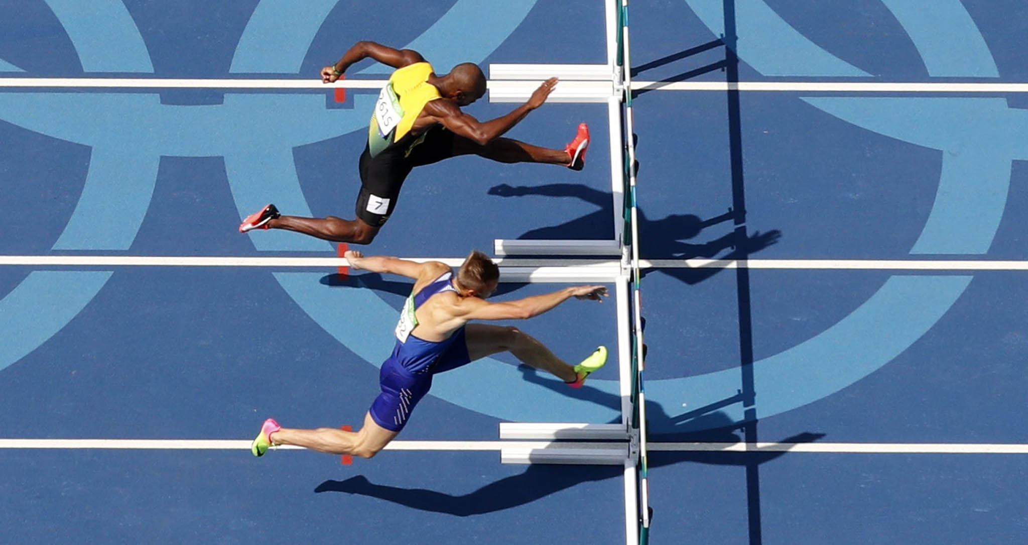 Competitors clear a hurdle during Round 1 of the Men's 40m Hurdles at the Olympic Stadium