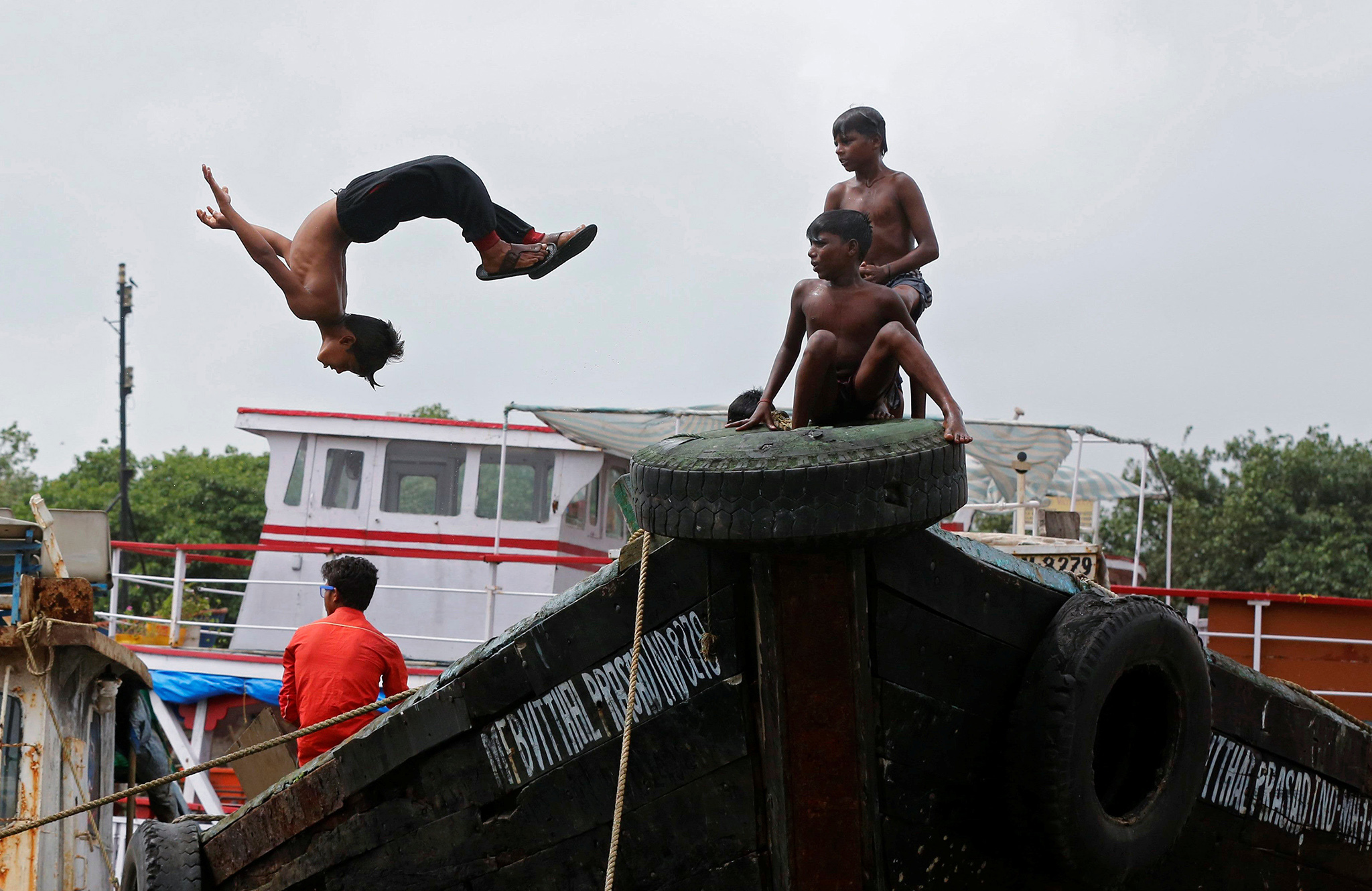 A boy dives off from a boat under maintenance in a dry dock in Mumbai, India